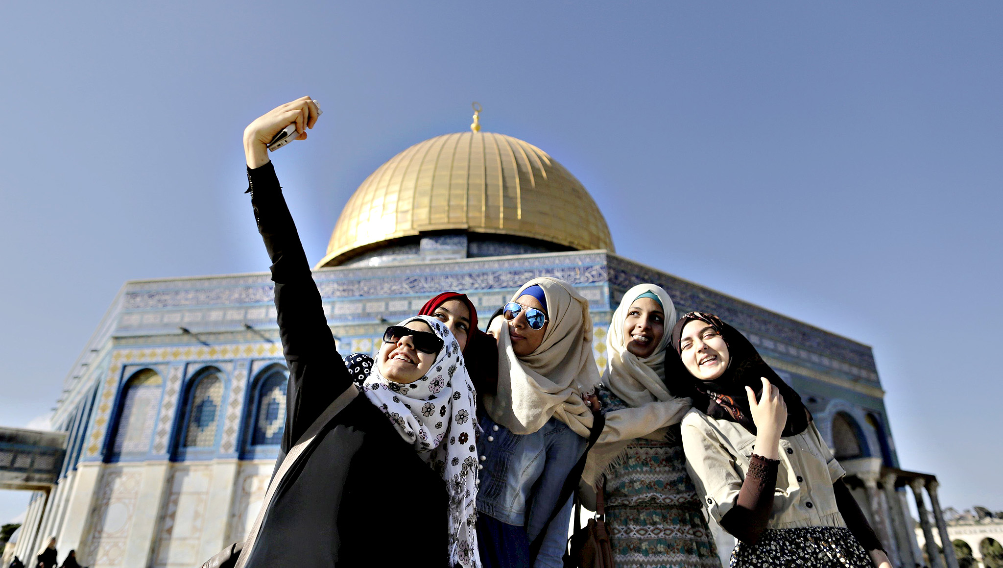 Palestinian Sanaa Abu Jaudi, from the West Bank city of Jenin, takes a selfie photo with friends in front of the Dome of the Rock on the compound known to Muslims as Noble Sanctuary and to Jews as Temple Mount, in Jerusalem's Old City, during the holy month of Ramadan