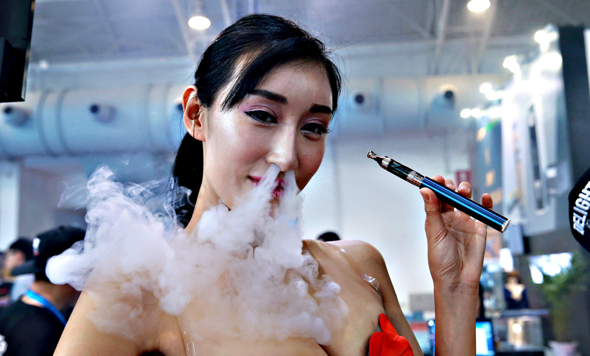 Sales staff exhaling vapour while demonstrating an electronic cigarette product at the Beijing International Vapor Distribution Alliance Expo, or the Vape China Expo, at the China International Exhibition Center in Beijing