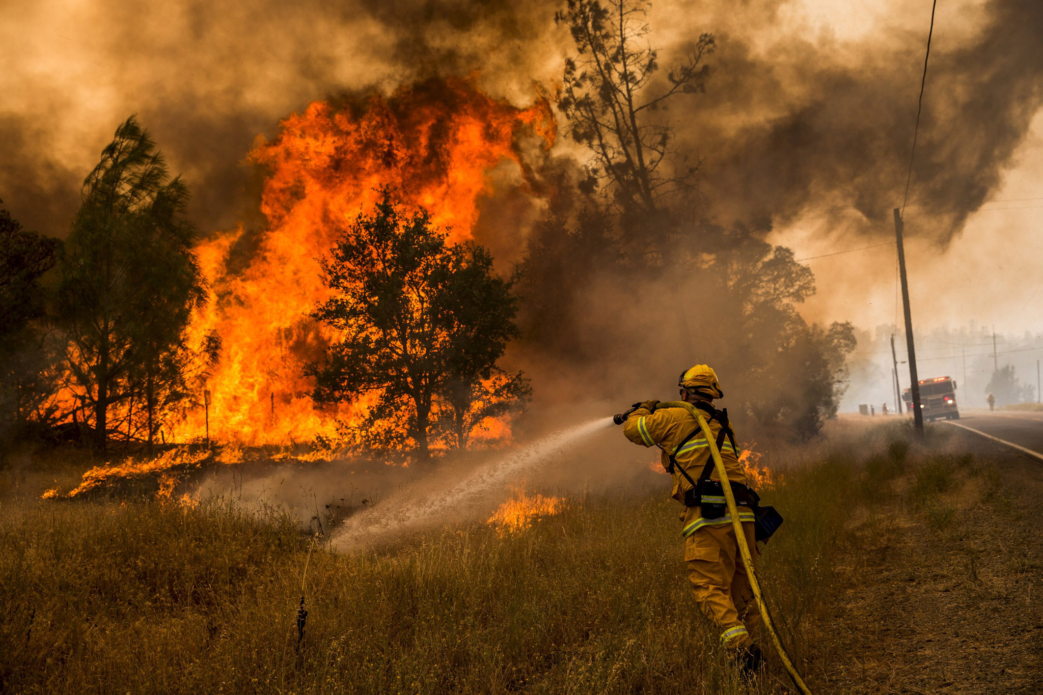 A firefighter battles a spot fire at the Rocky Fire in Lake County, California