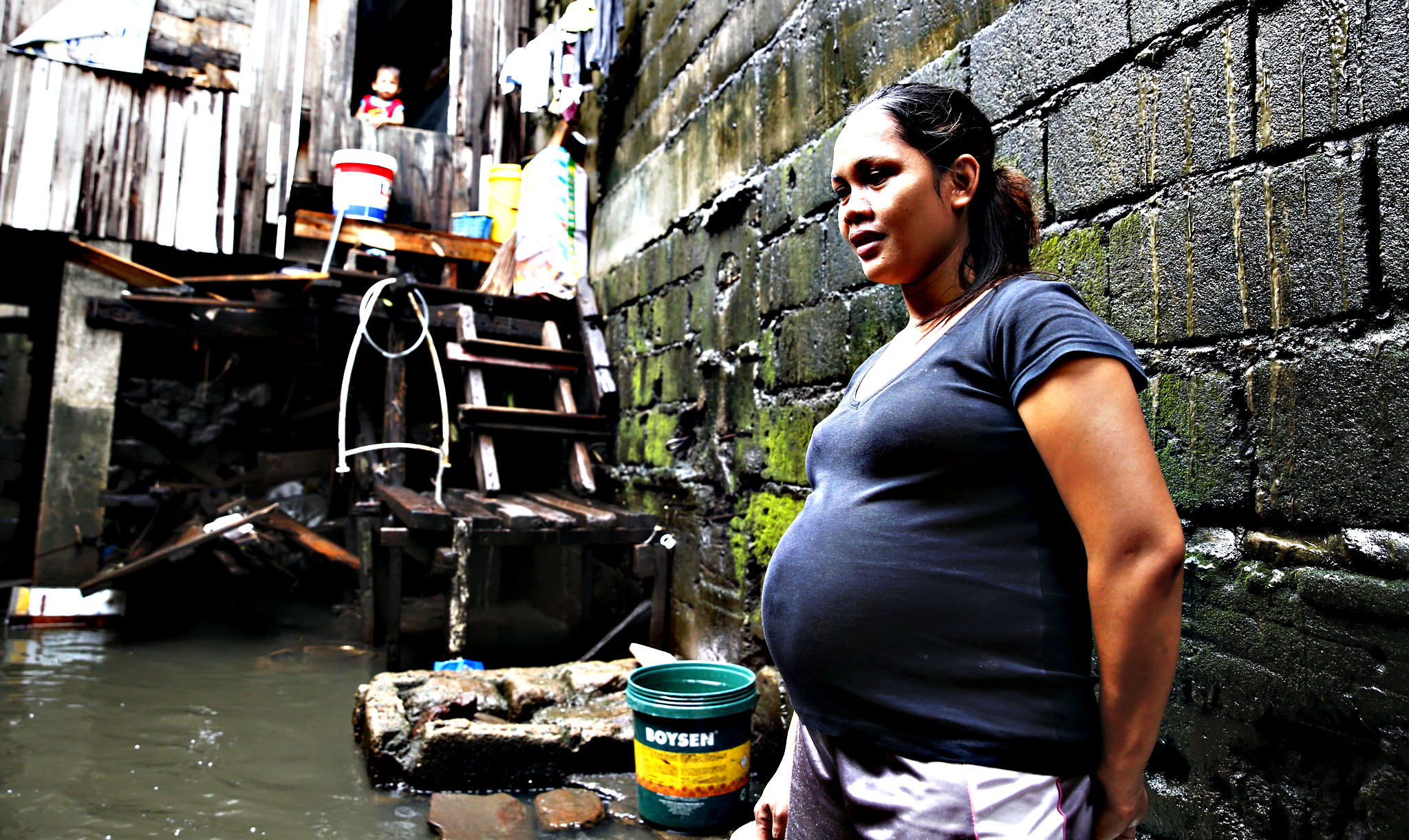 An eight-month pregnant woman stands near the entrance of her home at a flooded squatter colony beside a creek in Meycauayan Bulacan north of Manila in the Philippines July 10, 2015. The United Nations Population Fund, (UNFPA) called on humanitarian agencies to redouble efforts in addressing the special needs of vulnerable populations in preparedness and response measures to disasters as nations observe World Population Day on July 11