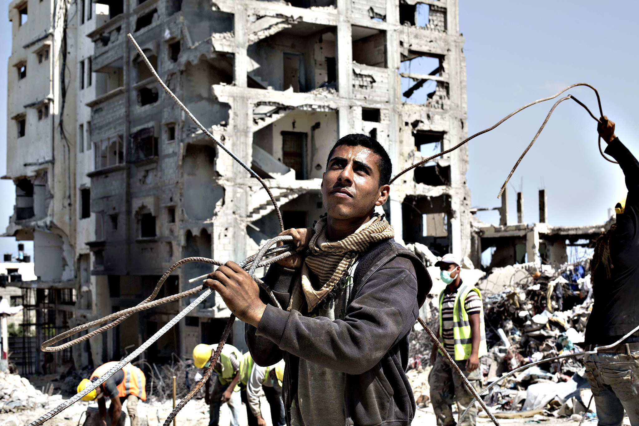 Palestinian workers remove iron from the rubble of a building that was destroyed during the 50-day war between Israel and Hamas' militants in the summer of 2014, in the al-Shejaeiya neighbourhood, east of Gaza City, on July 2, 2015.