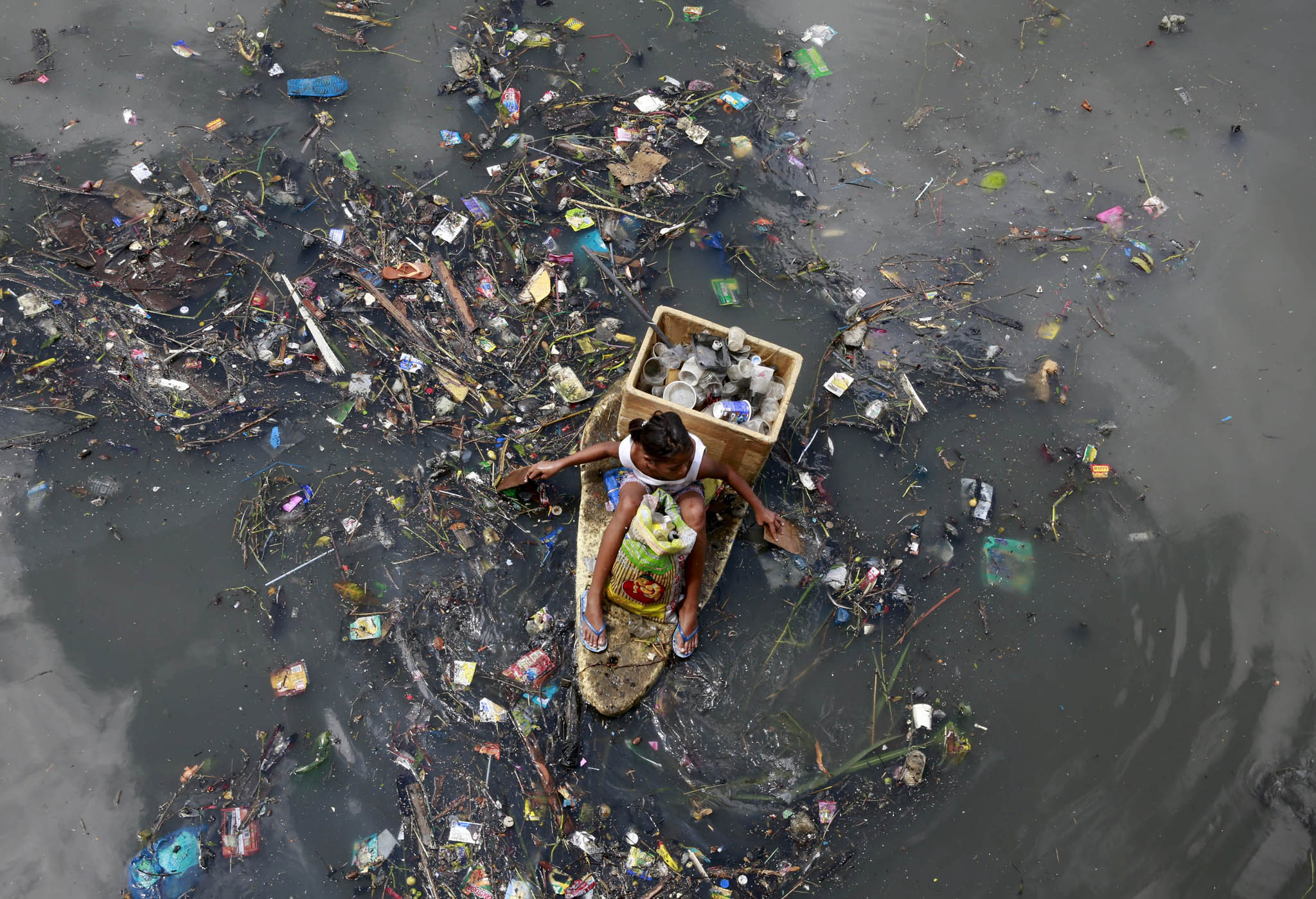A girl sits on a makeshift styrofoam raft as she collects recyclable material from floating garbage in a polluted river at Navotas city, north of Manila