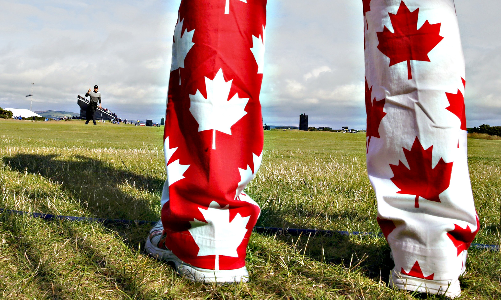 A spectator wearing trousers in the design of the Cnadaian flag watches as Graham DeLaet of Canada (L) makes a birdie on the ninth hole during the first round of the British Open golf championship on the Old Course in St. Andrews, Scotland...A spectator wearing trousers in the design of the Cnadaian flag watches as Graham DeLaet of Canada (L) makes a birdie on the ninth hole during the first round of the British Open golf championship on the Old Course in St. Andrews, Scotland, July 16, 2015.