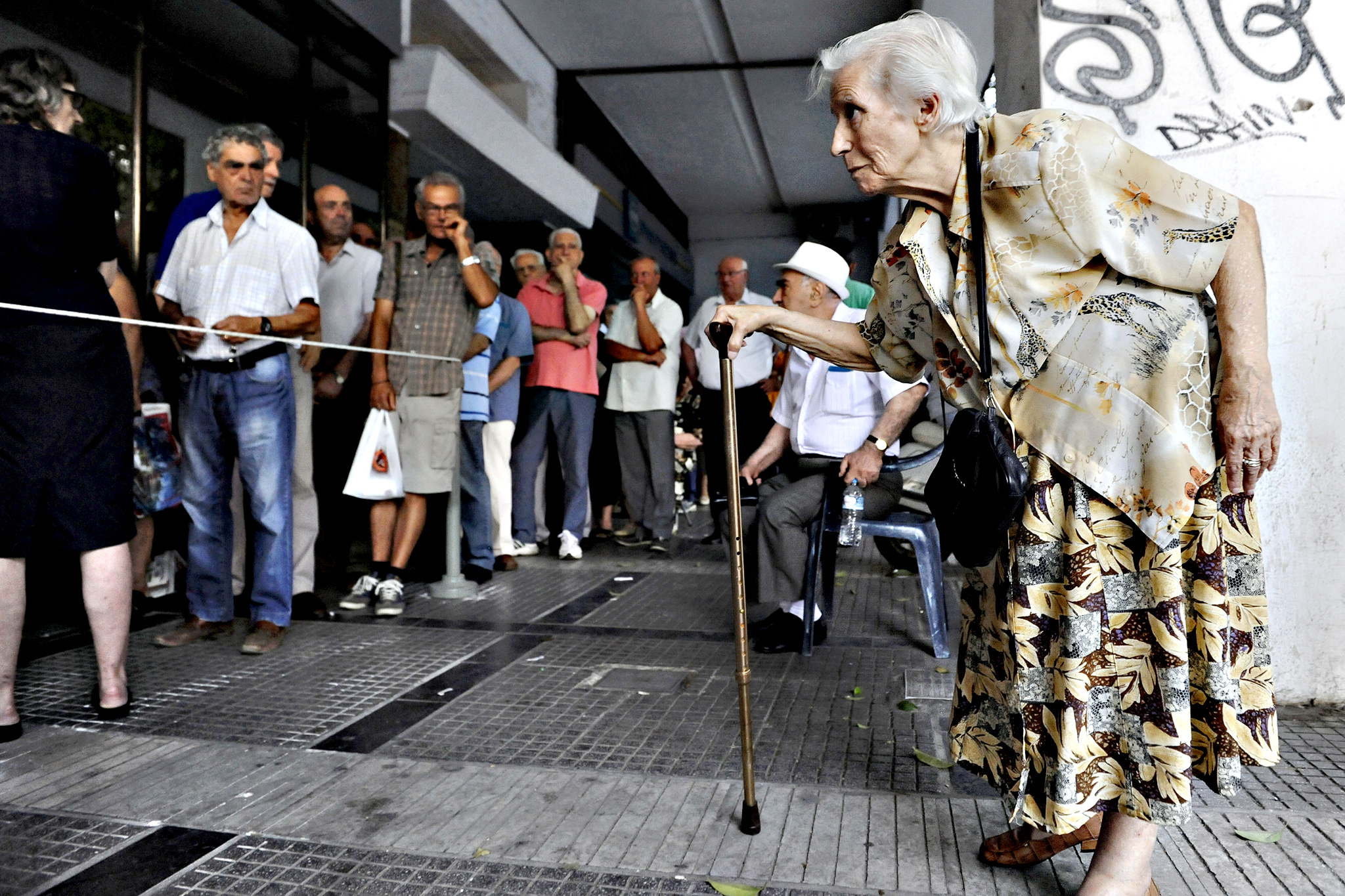 A pensioner (R) arrives at a National Bank branch to receive part of her pension at the city of Thessaloniki, Greece July 10, 2015.The Greek parliament will give the government a mandate to negotiate with creditors for a cash-for-reforms deal, the parliamentary spokesman of the ruling Syriza party told reporters on Friday