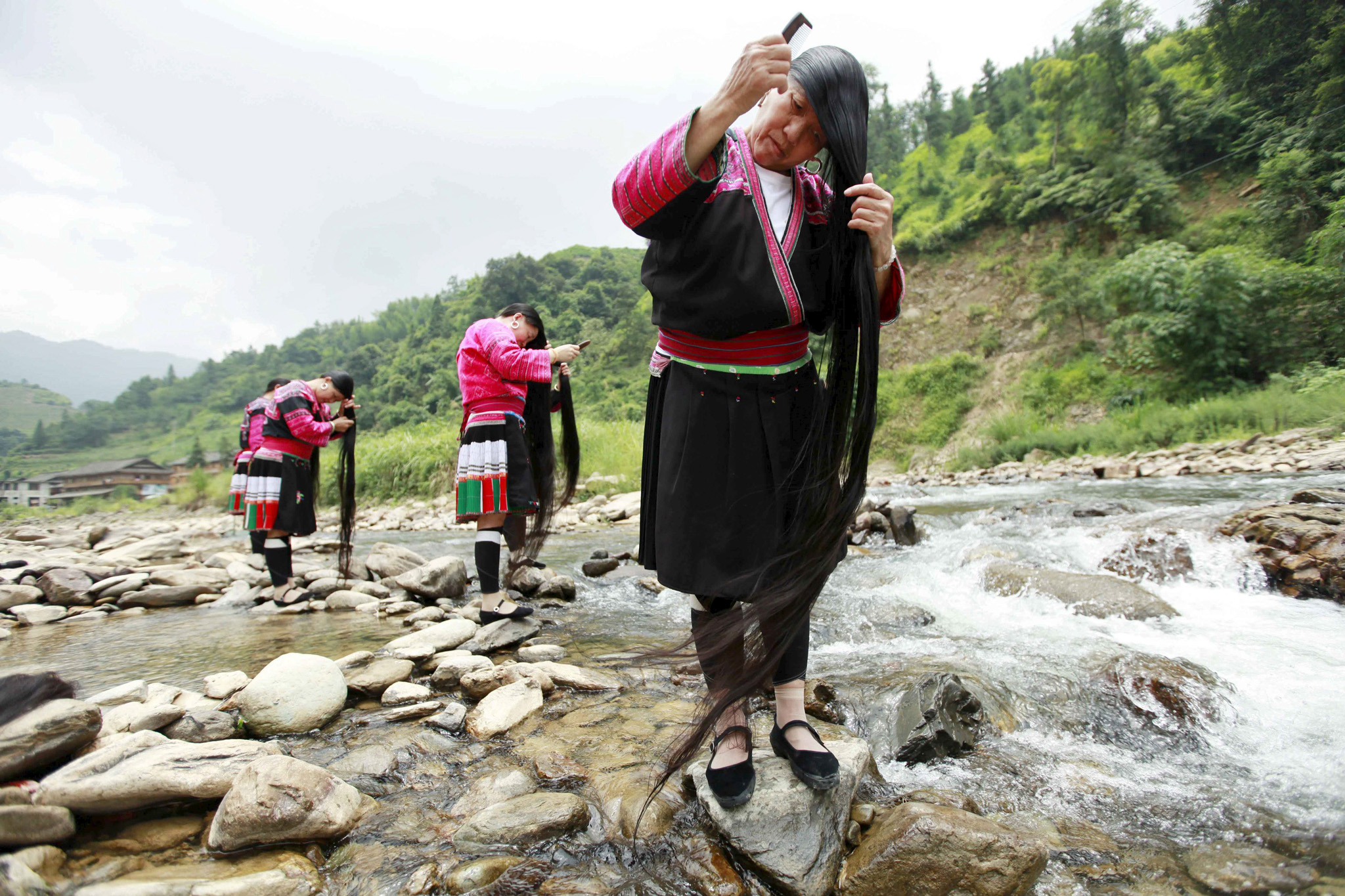 Ethnic Yao minority women brush their long hair near a creek, in Huangluo village of Guilin, Guangxi Zhuang Autonomous Region, China