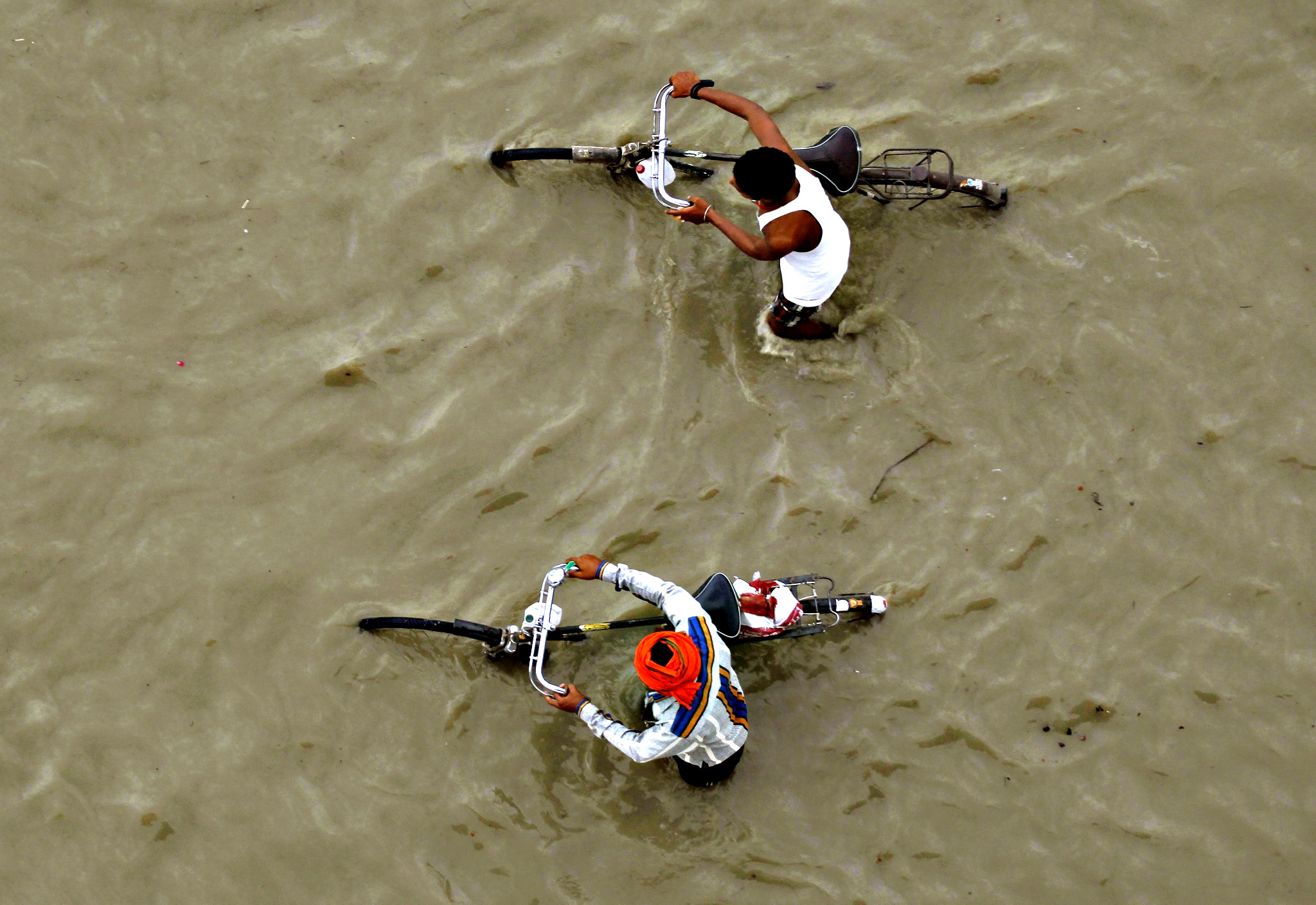 Men push their bicycles through the flooded banks of the river Ganges after heavy rains in Allahabad, India, on Thursday