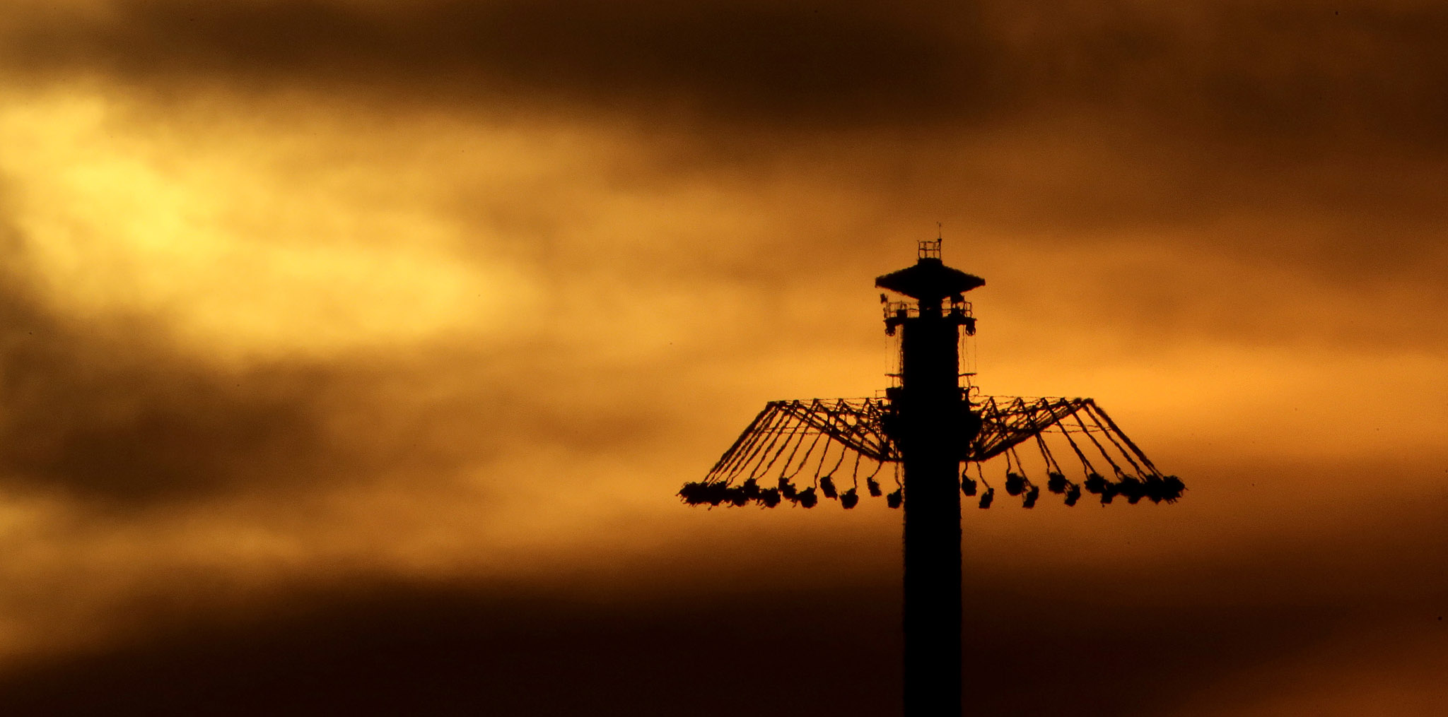 People riding an attraction are silhouetted as the sun sets beyond Worlds of Fun amusement park in Kansas City, Mo
