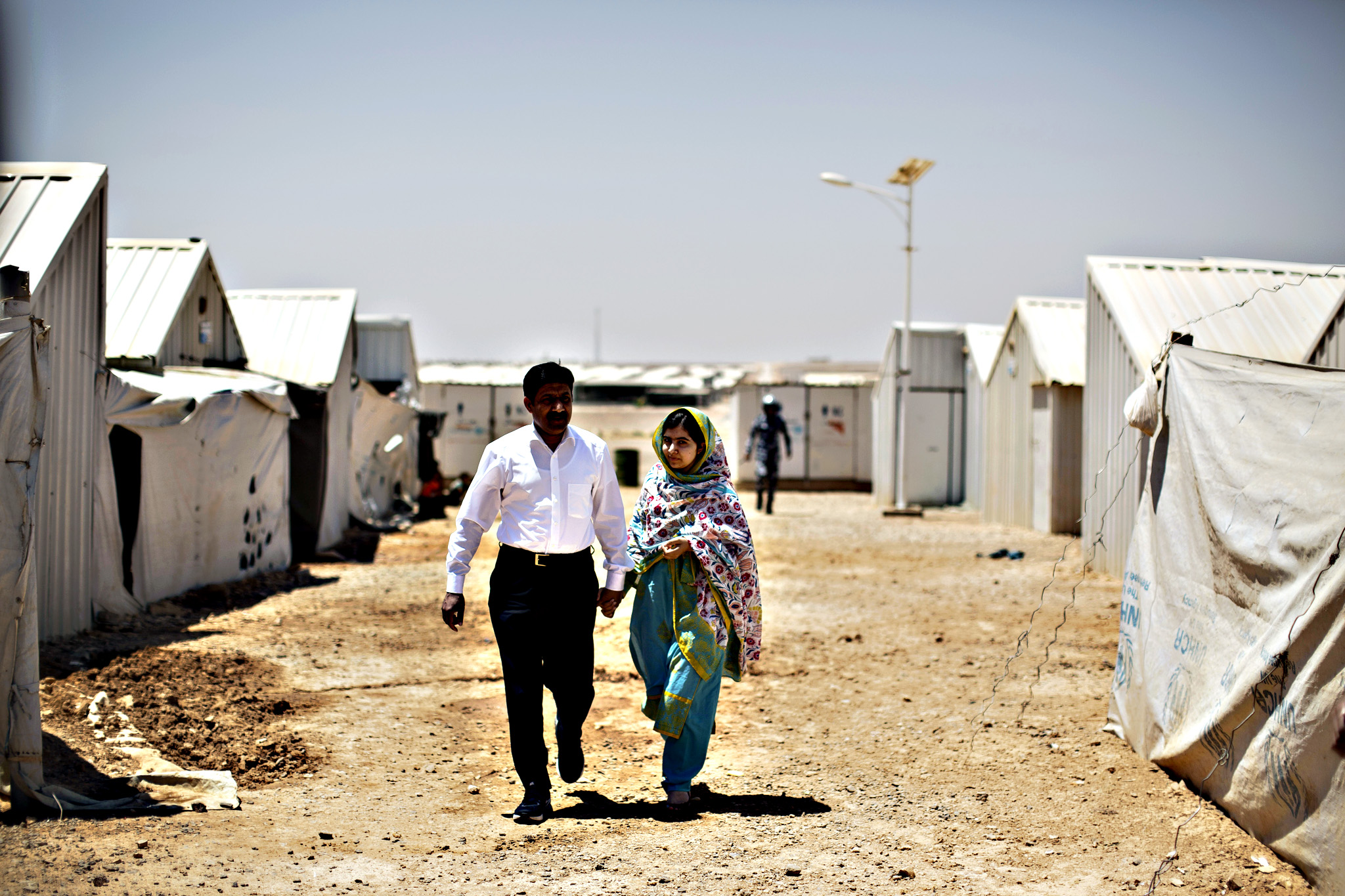 "Nobel Peace Prize laureate Malala Yousafzai, 18, left, and her father Ziauddin hold hands while walking in Azraq refugee camp, Jordan on Monday. Rich countries should spend less on weapons in the Syria conflict and more on education, Malala said Monday, calling world leaders ""quite stingy"" as she visited the camp for Syrian war refugees"