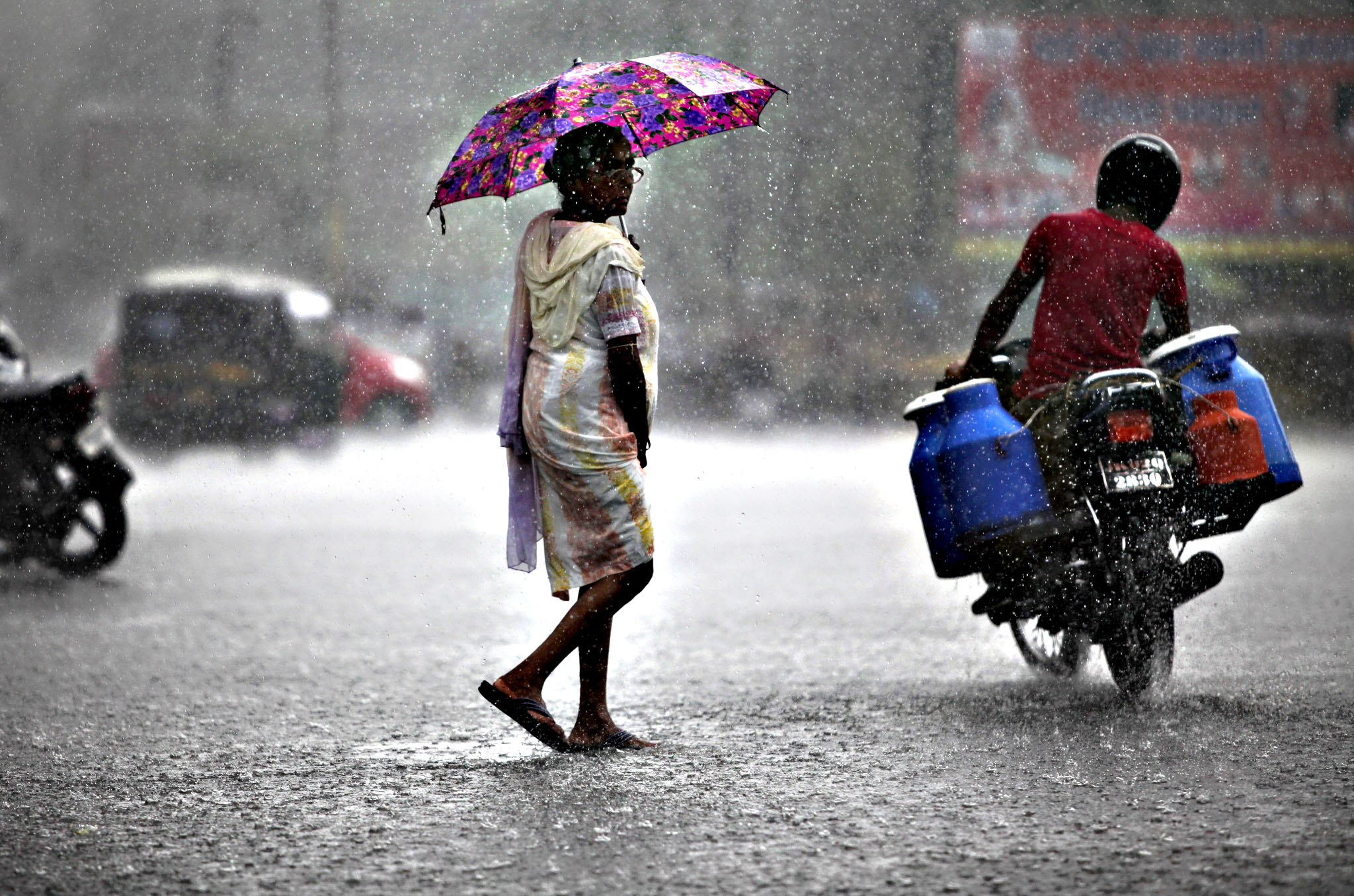 An Indian woman walks holding an umbrella during monsoon rains in Jammu, India, Tuesday, July 21, 2015. India receives the annual monsoon rains from June to September