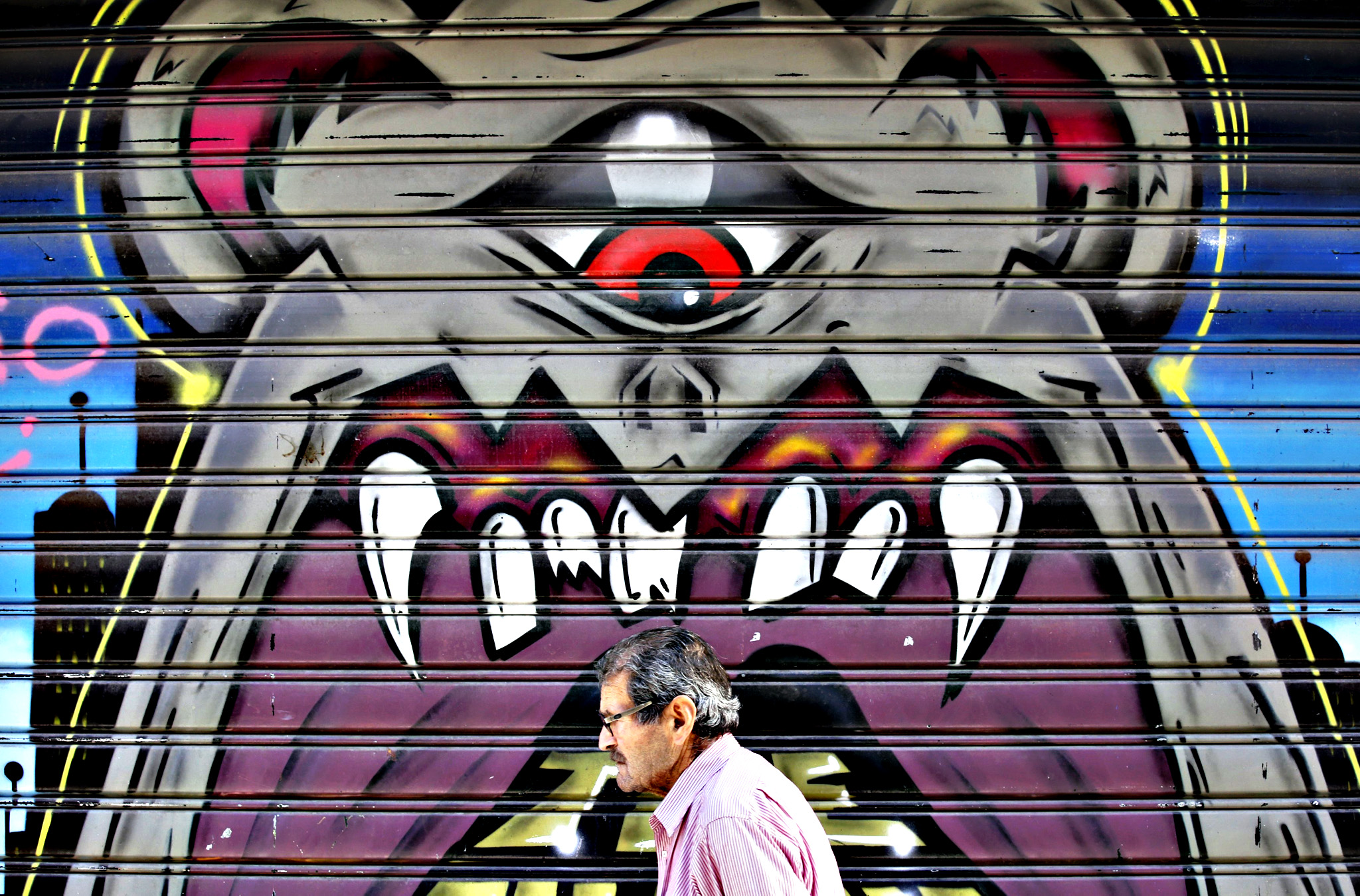 A man walks past graffiti painted on a closed shop at Monastiraki area in central Athens...A man walks past graffiti painted on a closed shop at Monastiraki area in central Athens, Greece, July 7, 2015. Greece faces a last chance to stay in the euro zone on Tuesday when Prime Minister Alexis Tsipras puts proposals to an emergency euro zone summit after Greek voters resoundingly rejected the austerity terms of a defunct bailout.