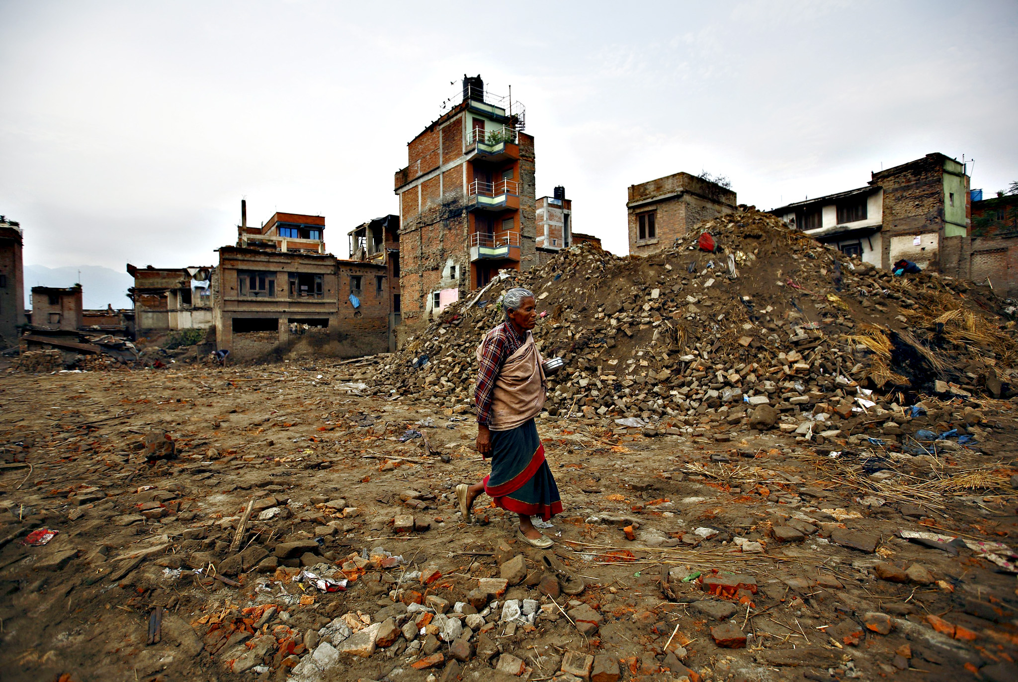 A woman walks past collapsed houses that were damaged during the earthquake in Bhaktapur July 14, 2015. Two months after massive twin earthquakes killed 8,897 people in Nepal, nearly three million survivors, many in mountainous, hard-to-reach areas, still needed shelter, food and basic medical care as the yearly monsoon bore down on the Himalayan nation, the U.N. said in a report released last week