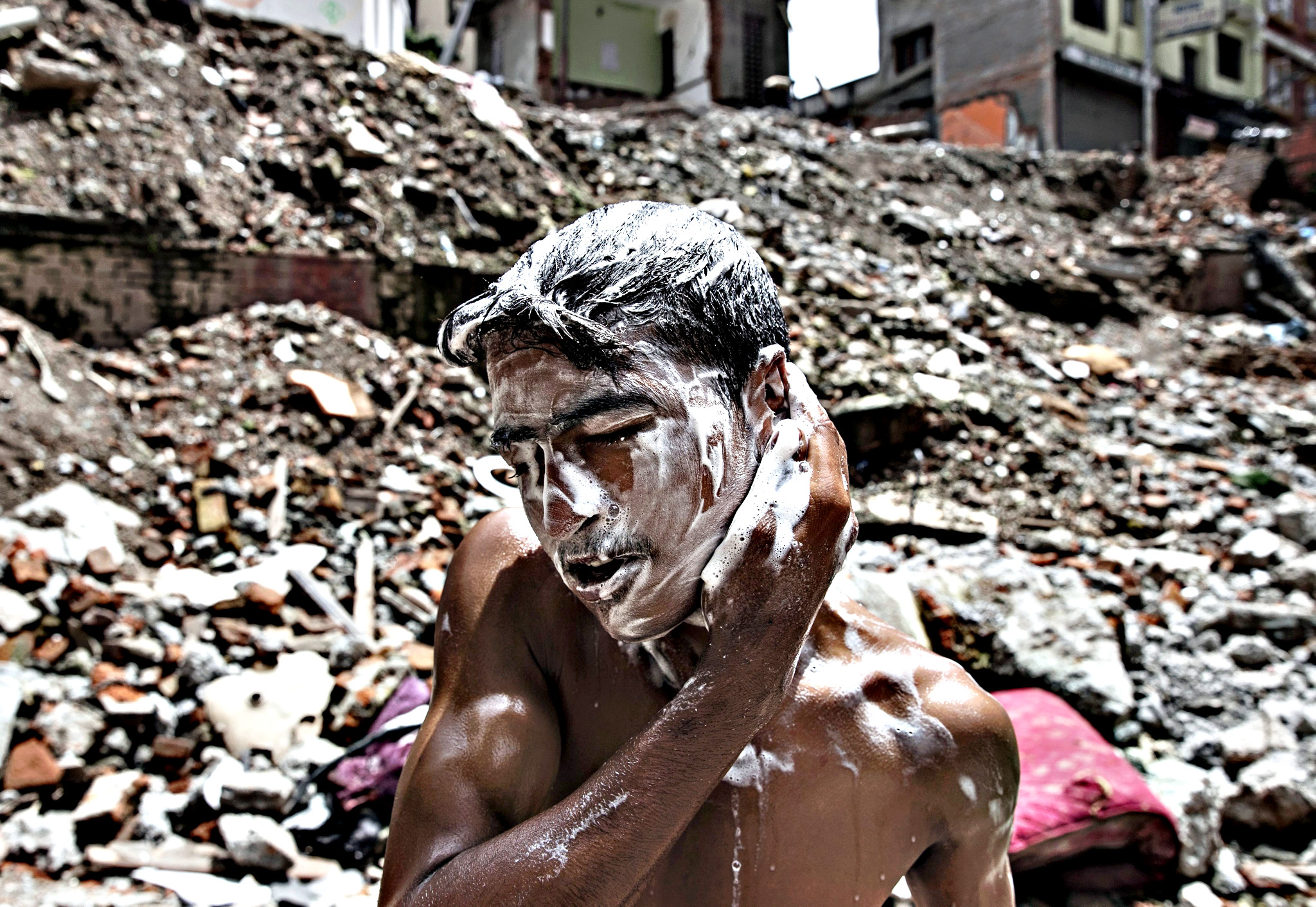 Nepalese boy Santosh Nepali, 15, washes himself at a damaged water spout in Thamel, Kathmandu, on Thursday. The historic spout was damaged during April earthquake