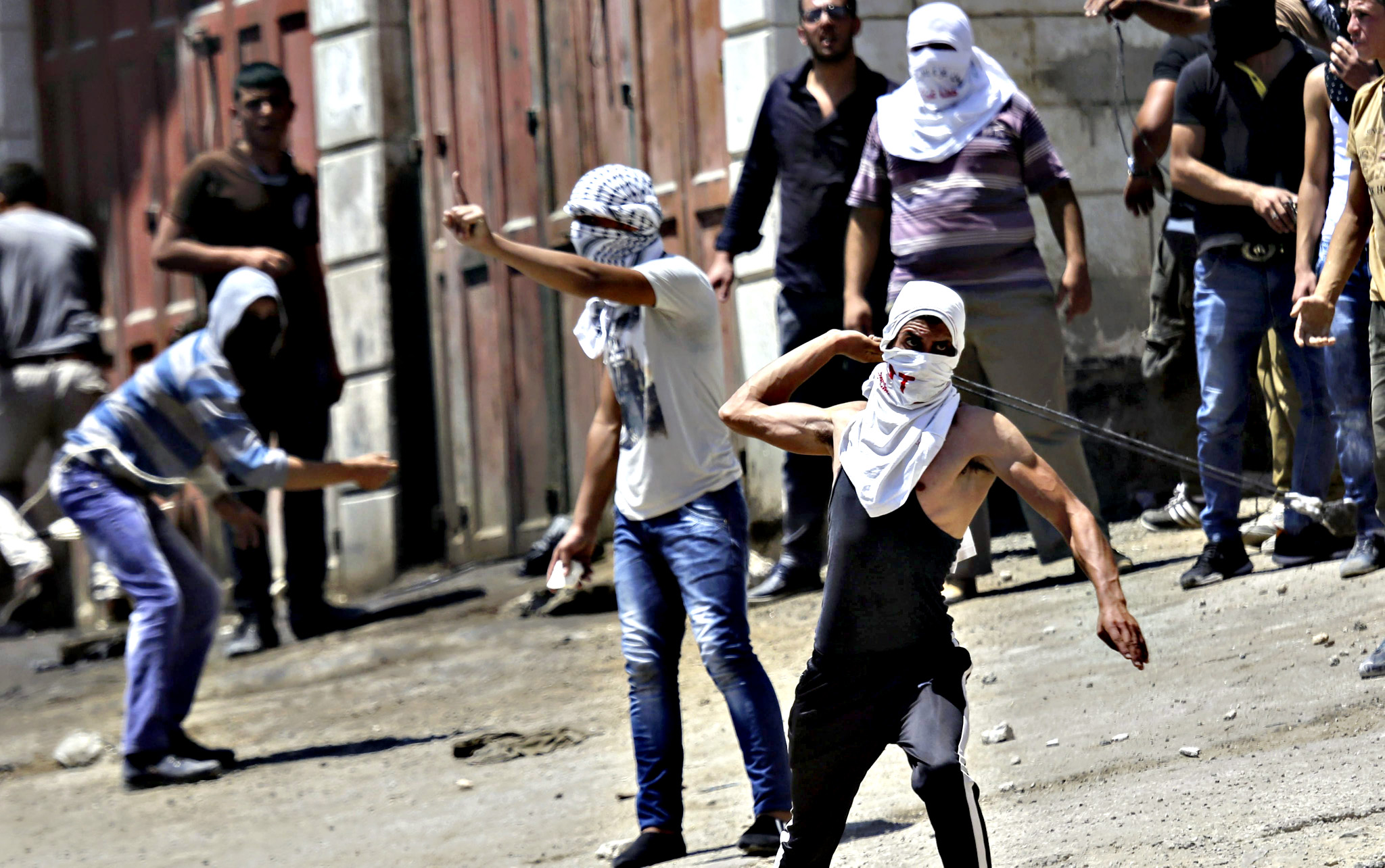 Palestinian protesters from the village of Beit Ummar near Hebron, West Bank, clash with Israeli soldiers in the village on 23 July 2015. Following the funeral of Falah Abu Maria, 53, who was shot dead by  Israeli soldiers during a raid on his home early 23 July 2015 to arrest his son, in the southern West Bank town of Beit Ummar. The man's two sons, both in their 20s, were injured in the raid