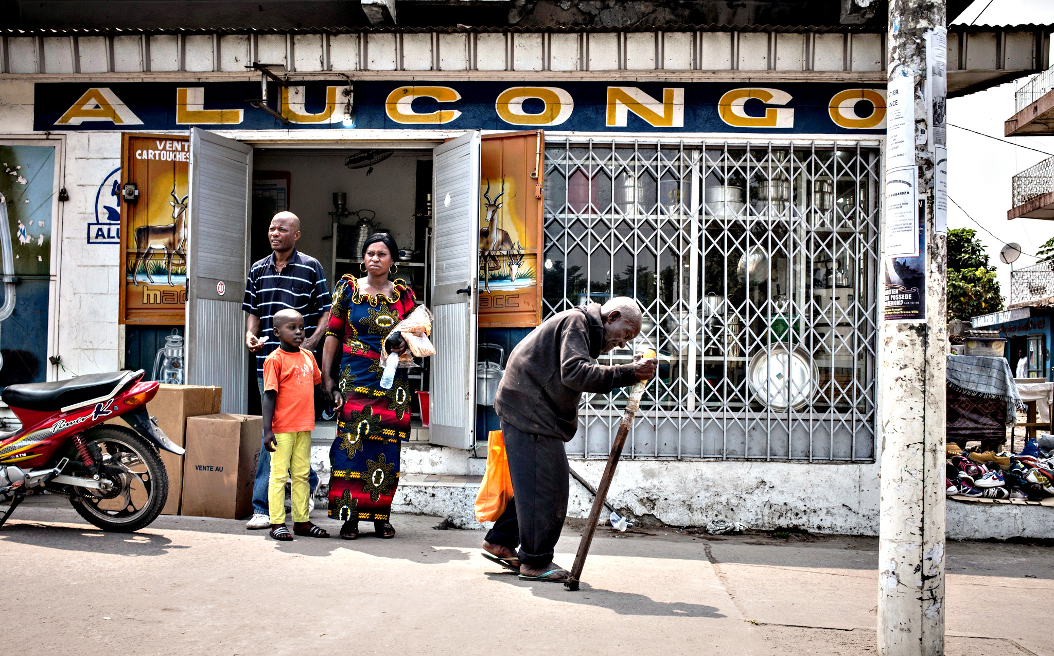 A man uses a cane as he walks past a store in the Poto Poto popular district, of the Congolese capital Brazzaville
