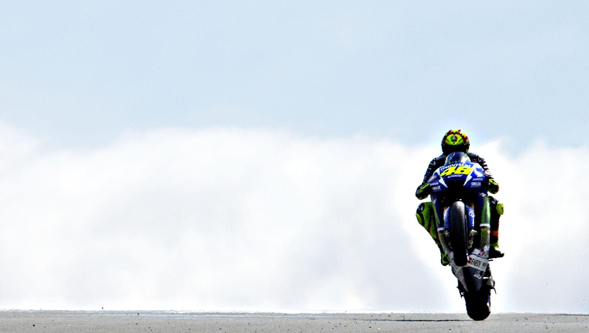 Yamaha rider Valentino Rossi of Italy pulls a wheelie during the first training session of the MotoGP Grand Prix of Germany at the Sachsenring Circuit on July 10, 2015 in Hohenstein-Ernstthal, eastern Germany.