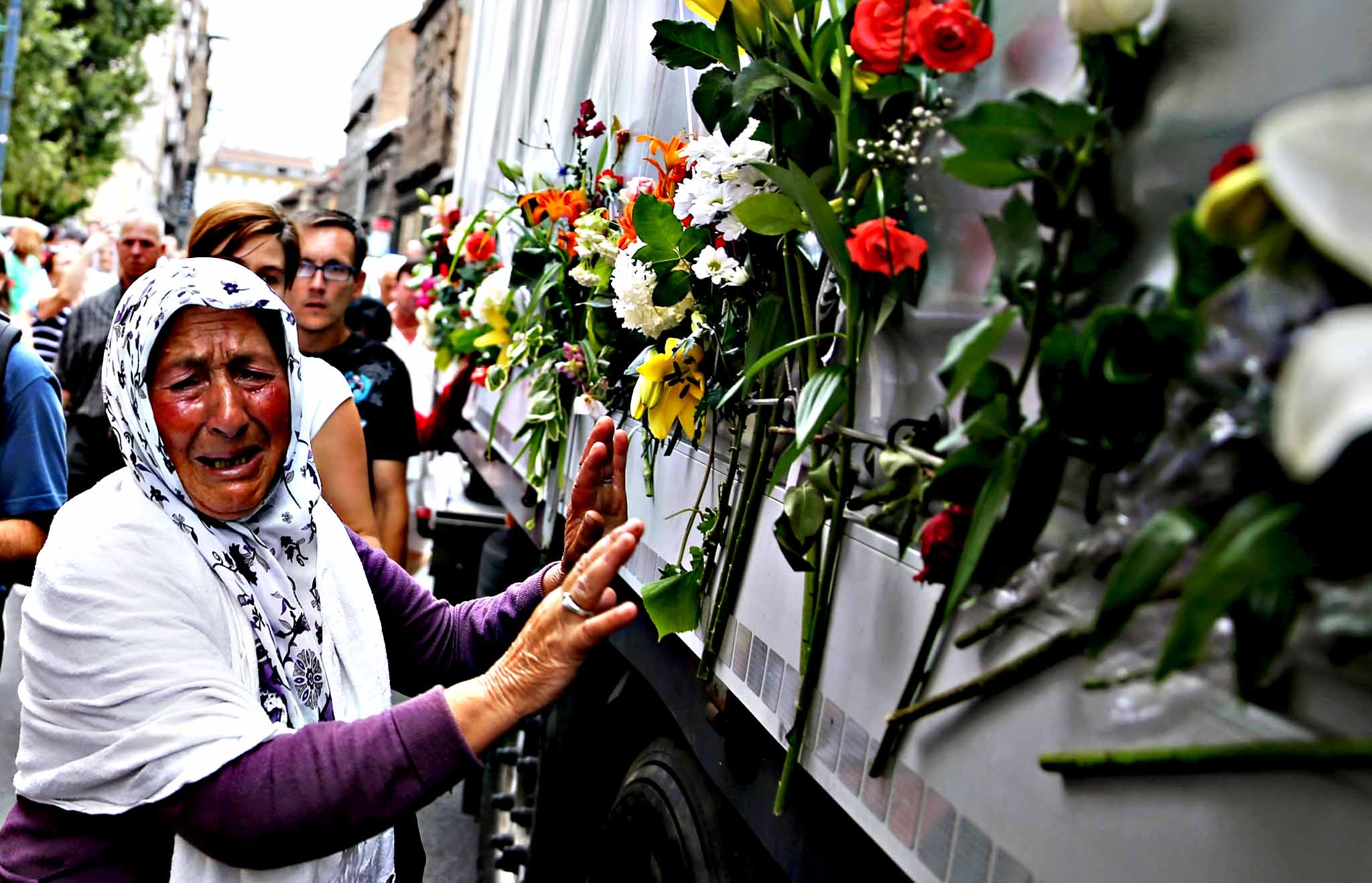 A woman cries beside a truck carrying 136 coffins of newly identified victims of the 1995 Srebrenica massacre, in front of the presidential building in Sarajevo...A woman cries beside a truck carrying 136 coffins of newly identified victims of the 1995 Srebrenica massacre, in front of the presidential building in Sarajevo July 9, 2015. The bodies of the 136 recently identified victims of Srebrenica massacre will be transported to the memorial centre in Potocari where they will be buried on July 11, the anniversary of the massacre when Bosnian Serb forces slaughtered 8,000 Muslim men and boys and buried them in mass graves in Europe's worst massacre since World War Two