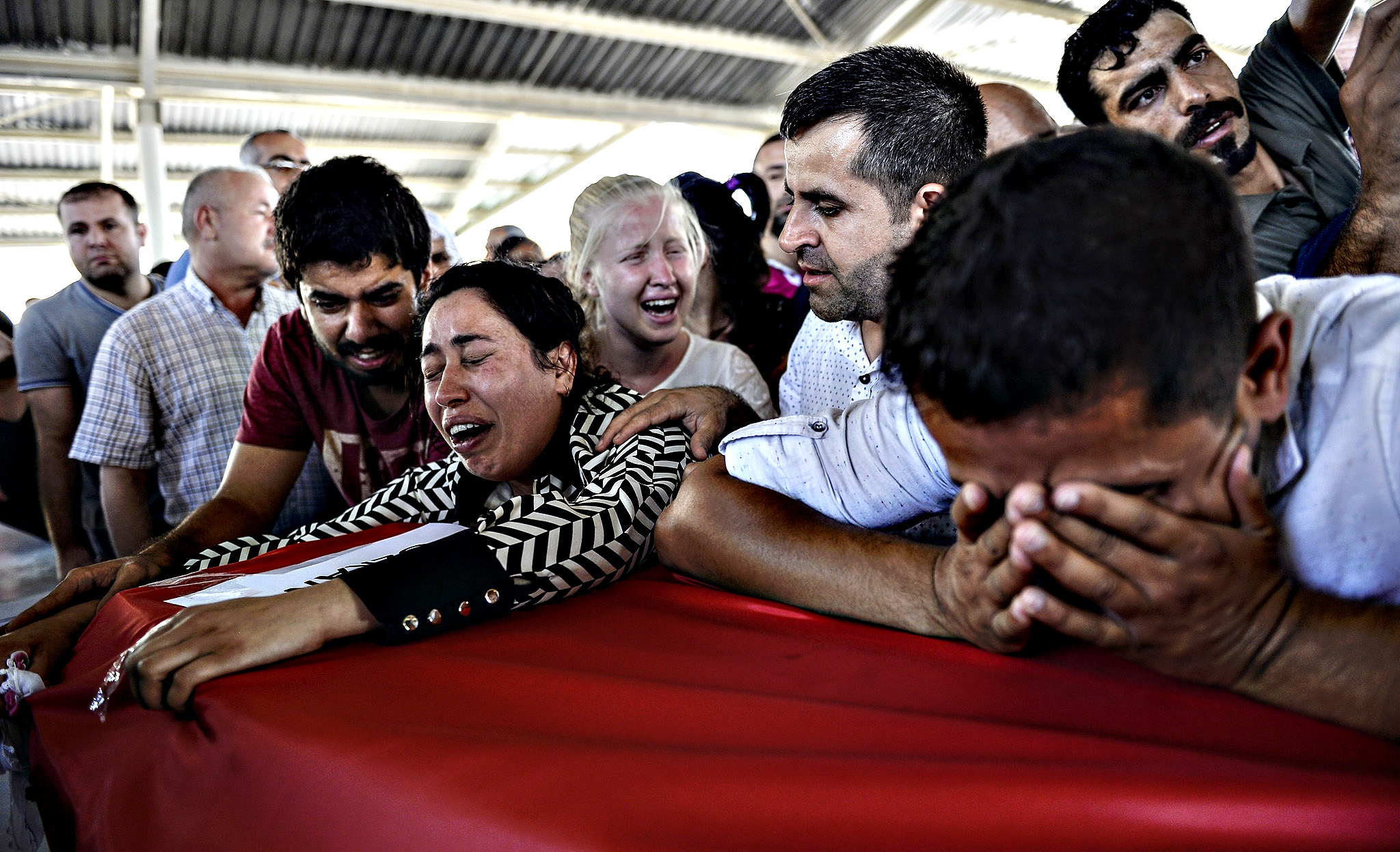 Mourners react over coffins in Gaziantep on July 21, 2015, during a funeral ceremony for victims following a suicide bomb attack the day before which killed at least 31 in the southern Turkish town of Suruc. A suspected Islamic State suicide bomber killed at least 31 people in an attack on a Turkish cultural centre in the southern town of Suruc, where activists had gathered to prepare for an aid mission in the nearby Syrian town of Kobane. It was one of the deadliest attacks in Turkey in recent years and the first time the government has directly accused the IS group of carrying out an act of terror on Turkish soil