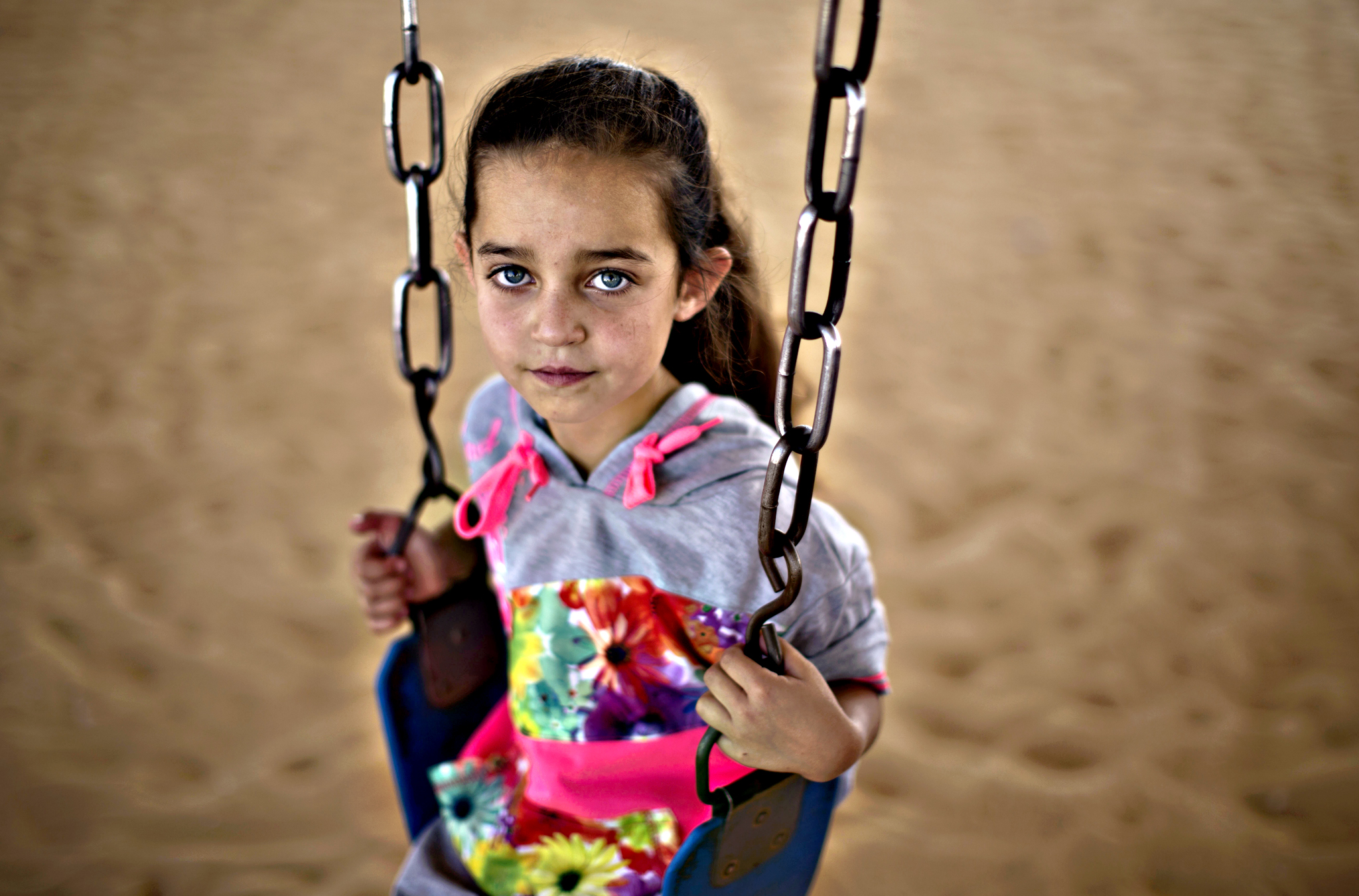 Syrian refugee Heba Ahmad, 7, pauses while playing on a swing with other children on the first day of the Eid al-Fitr holiday that marks the end of the holy fasting month of Ramadan at Zaatari refugee camp, in Mafraq, Jordan, Friday, July 17, 2015.