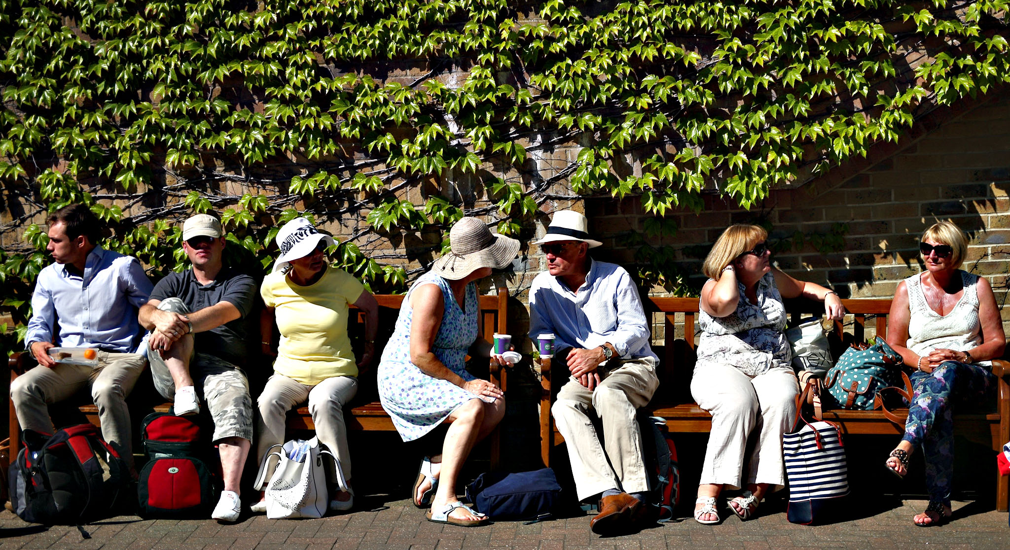 People relax in the sun as they queue to attend day 11 of the Wimbledon Lawn Tennis Championships at the All England Lawn Tennis and Croquet Club on July 10, 2015 in London, England. The 129th tournament to be hosted at Wimbledon is due to run for two weeks from Monday 29th June