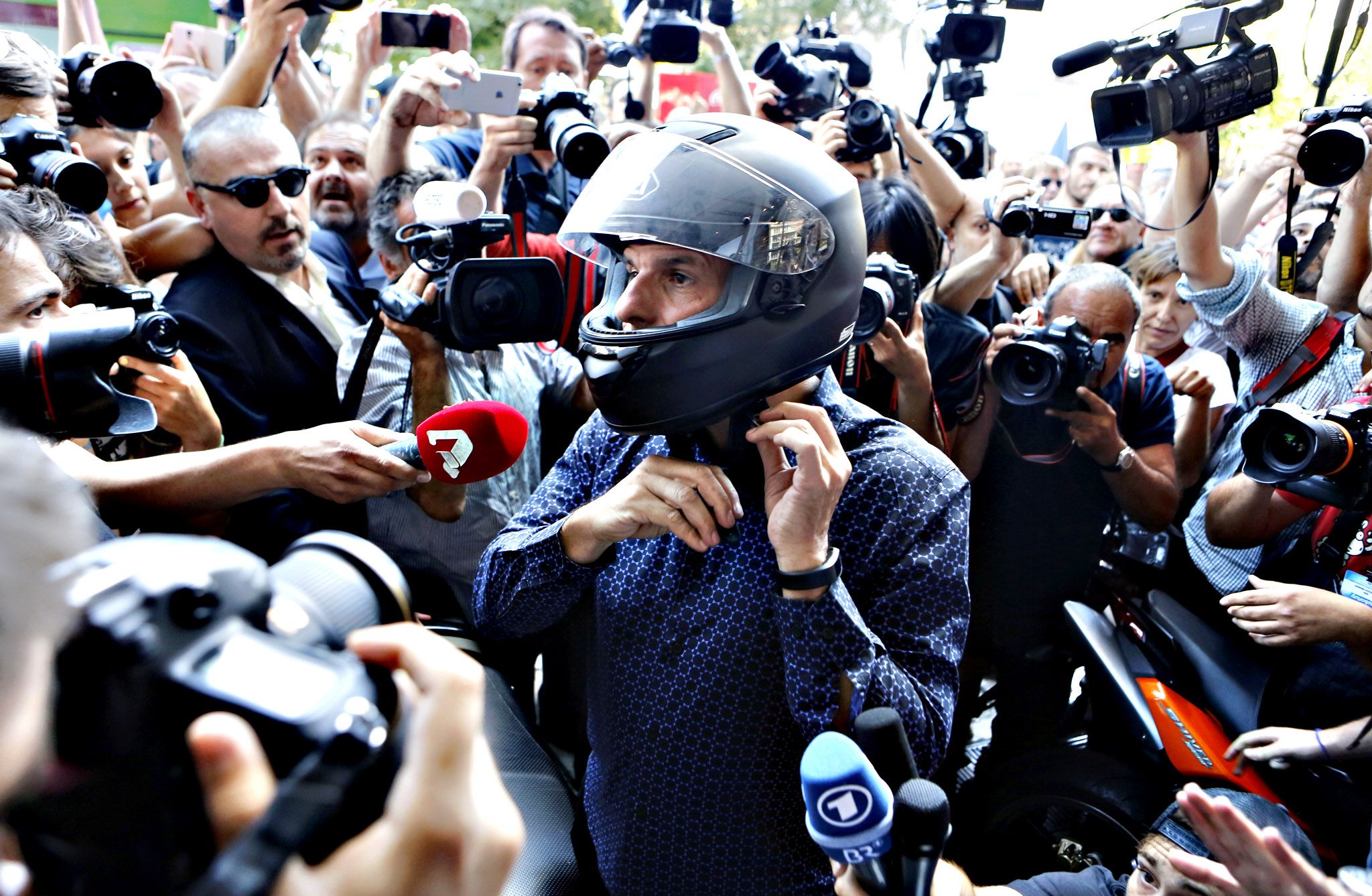 Outgoing Greek Finance Minister Yanis Varoufakis puts his helmet on as he is surrounded by media after his resignation in Athens, Monday, July 6, 2015. Greece and its membership in Europe's joint currency faced an uncertain future Monday, with the country under pressure to reach a bailout deal with creditors as soon as possible after Greeks resoundingly rejected the notion of more austerity in exchange for aid.