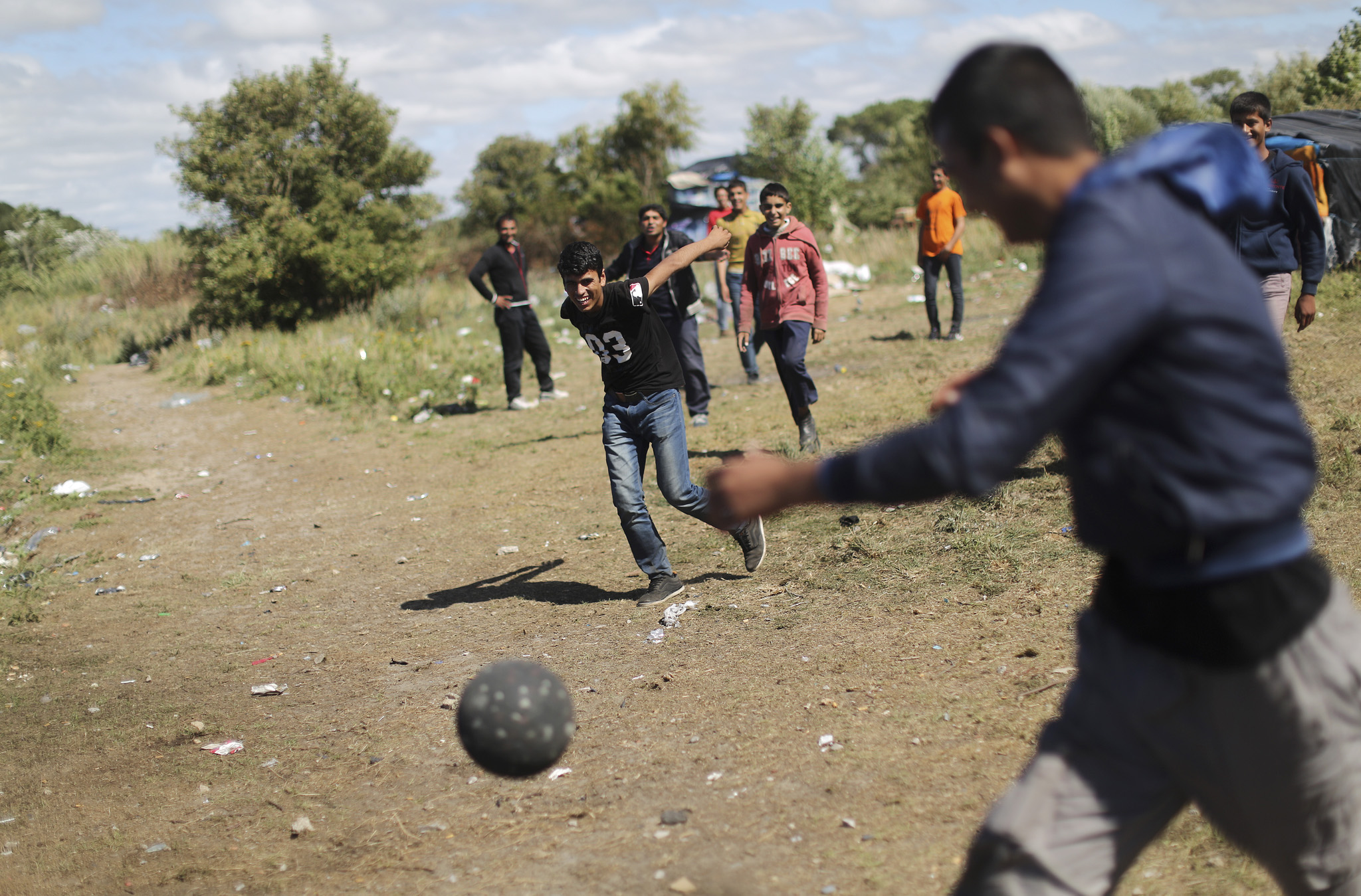 "In the ""new jungle"" migrant camp, close to the port of Calais. Afghan boys pass the time with a game of football."