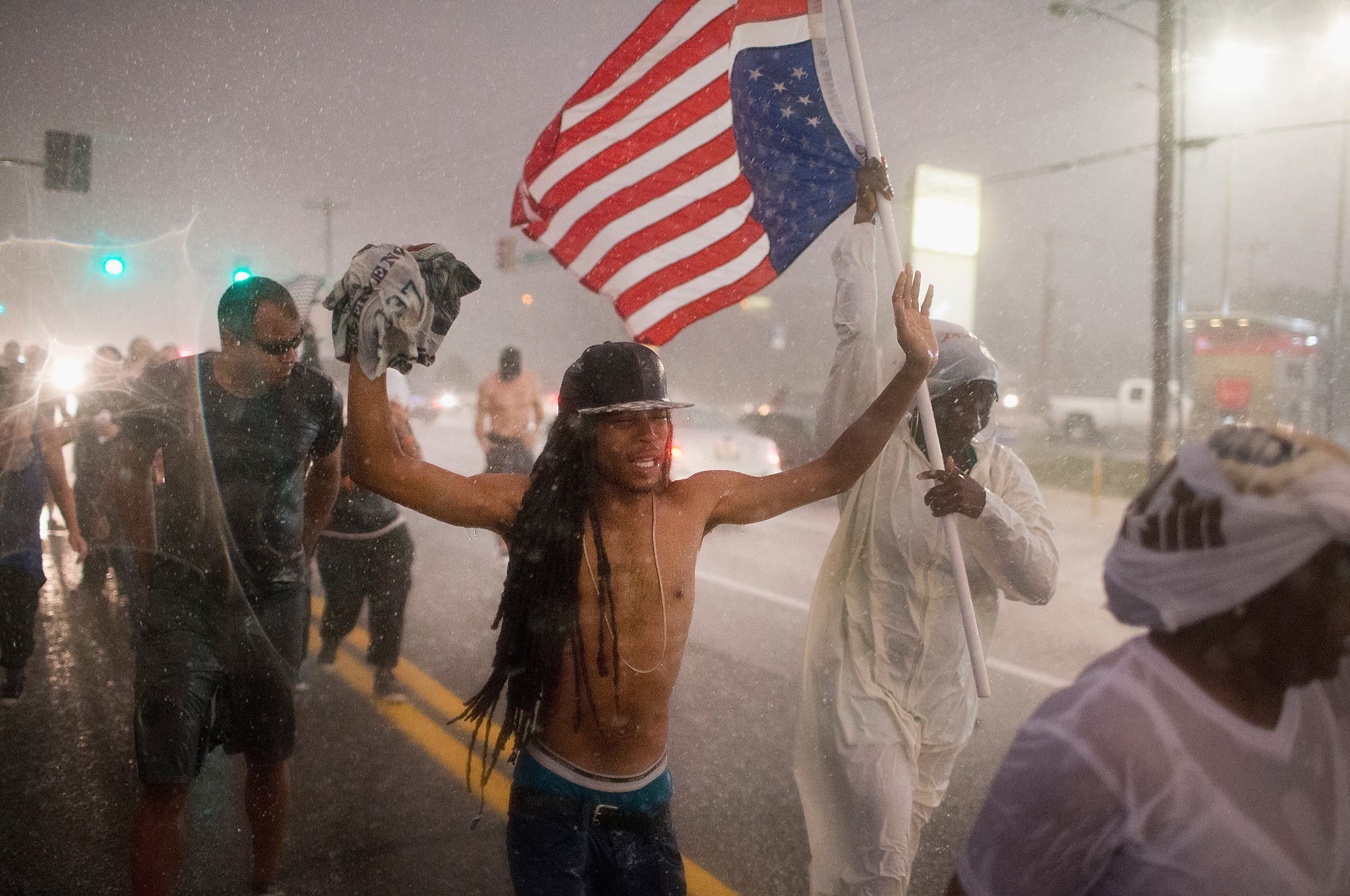 Ferguson, Missouri Marks One-Year Anniversary Of The Death Of Michael Brown...FERGUSON, MO - AUGUST 09:  Demonstrators, marking the one-year anniversary of the shooting of Michael Brown, march along West Florrisant Street in a driving rain on August 9, 2015 in Ferguson, Missouri. There are reports that two people were shot when gun fire broke out during protests later in the evening. Brown was shot and killed by a Ferguson police officer on August 9, 2014. His death sparked months of sometimes violent protests in Ferguson and drew nationwide focus on police treatment of black offenders.  (Photo by Scott Olson/Getty Images)
