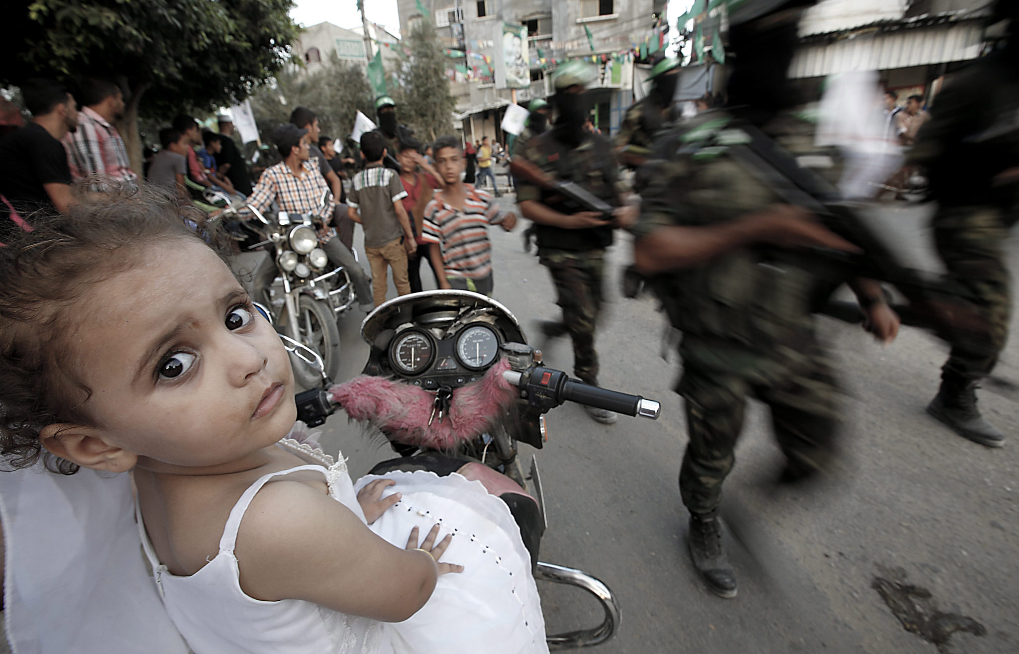 Hamas militants parade...epa04880536 Three-year-old Nour Al Masri (L) watches as the Ezz Al-Din Al-Qassam militia, the military wing of the Hamas movement,  parades in the streets of Beit Hanun in the northern Gaza Strip, 11 August 2015.  EPA/MOHAMMED SABER