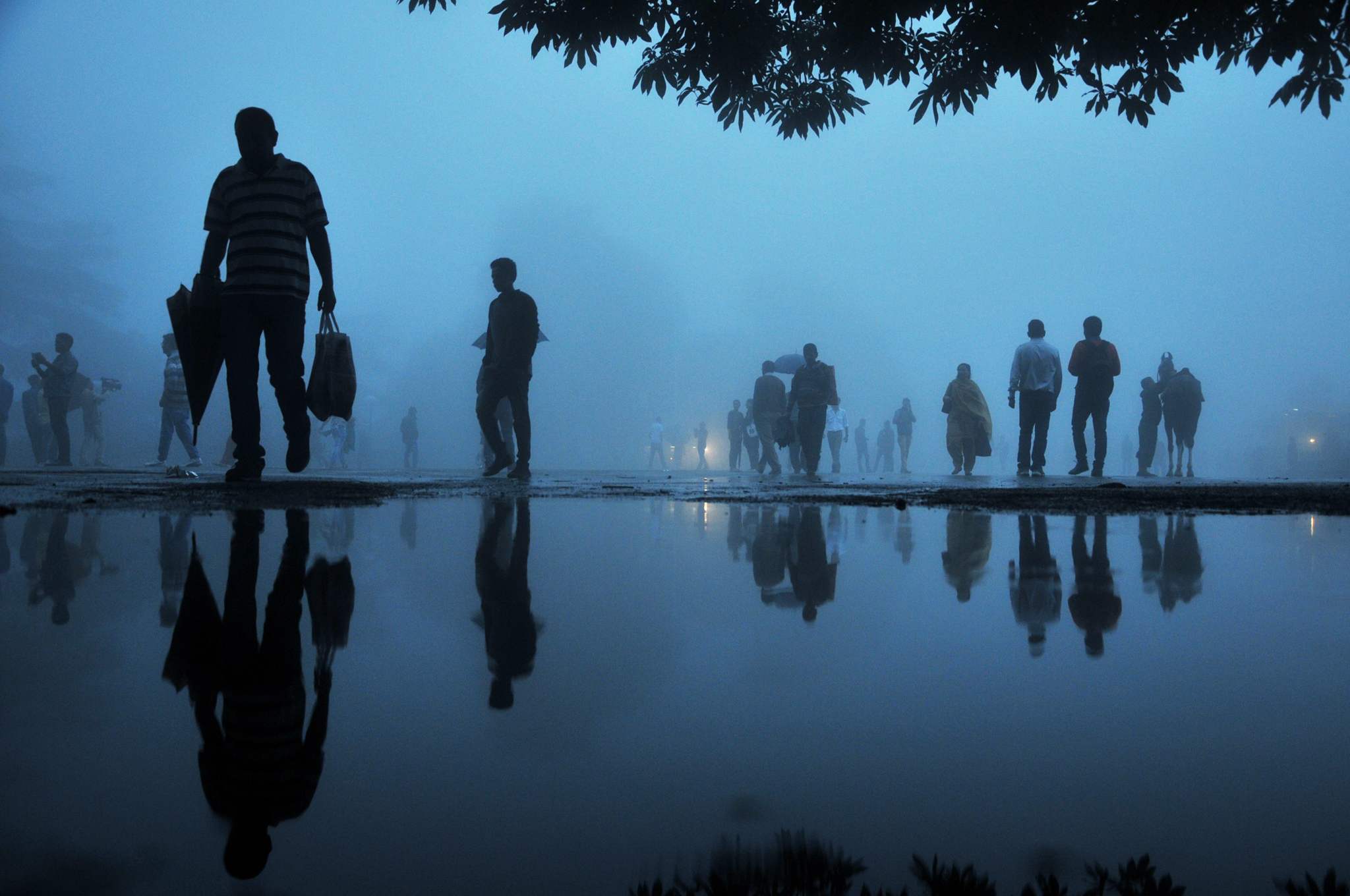 Indian pedestrians are reflected in a puddle after a rainfall in the northern hill town of Shimla on August 20, 2105. AFP PHOTO / STRSTRDEL/AFP/Getty Images