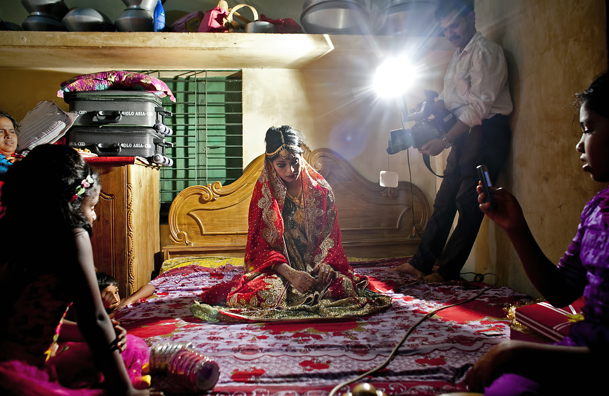 "Child Marriage In Bangladesh...MANIKGANJ, BANGLADESH - AUGUST 20: 15 year old Nasoin Akhter poses for a video on the day of her wedding to a 32 year old man, August 20, 2015 in Manikganj, Bangladesh.  In June of this year, Human Rights Watch released a damning report about child marriage in Bangladesh. The country has one of the highest rates of child marriage in the world, with 29% of girls marrying before the age of 15, and 65% of girls marrying before they turn 18. The detrimental effects of early marriage on a girl cannot be overstated. Most young brides drop out of school. Pregnant girls from 15-20 are twice as likely to die in childbirth than those 20 or older, while girls under 15 are at five times the risk. Research cites spousal age difference as a significant risk factor for violence and sexual abuse. Child marriage is attributed to both cultural tradition and poverty. Parents believe that it ""protects"" girls from sexual assault and harassment. Larger  dowries are not required for young girls, and economically, women's earnings are insignificant as compared to men's. (Photo by Allison Joyce/Getty Images)"