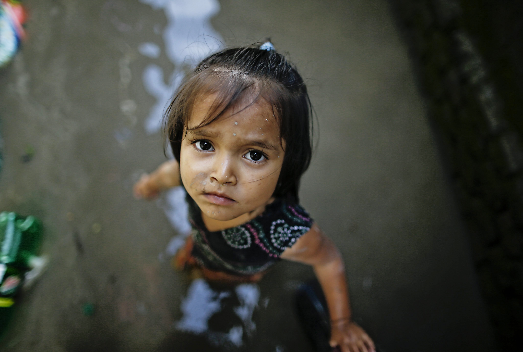 epa04887005 A girl stands amid floodwaters at her flooded home in a squatters' area after heavy rains in Kathmandu, Nepal, 17 August 2015. Hundreds of houses at a Bagmati squatters' settlement became waterlogged after the Bagmati River burst its banks.
