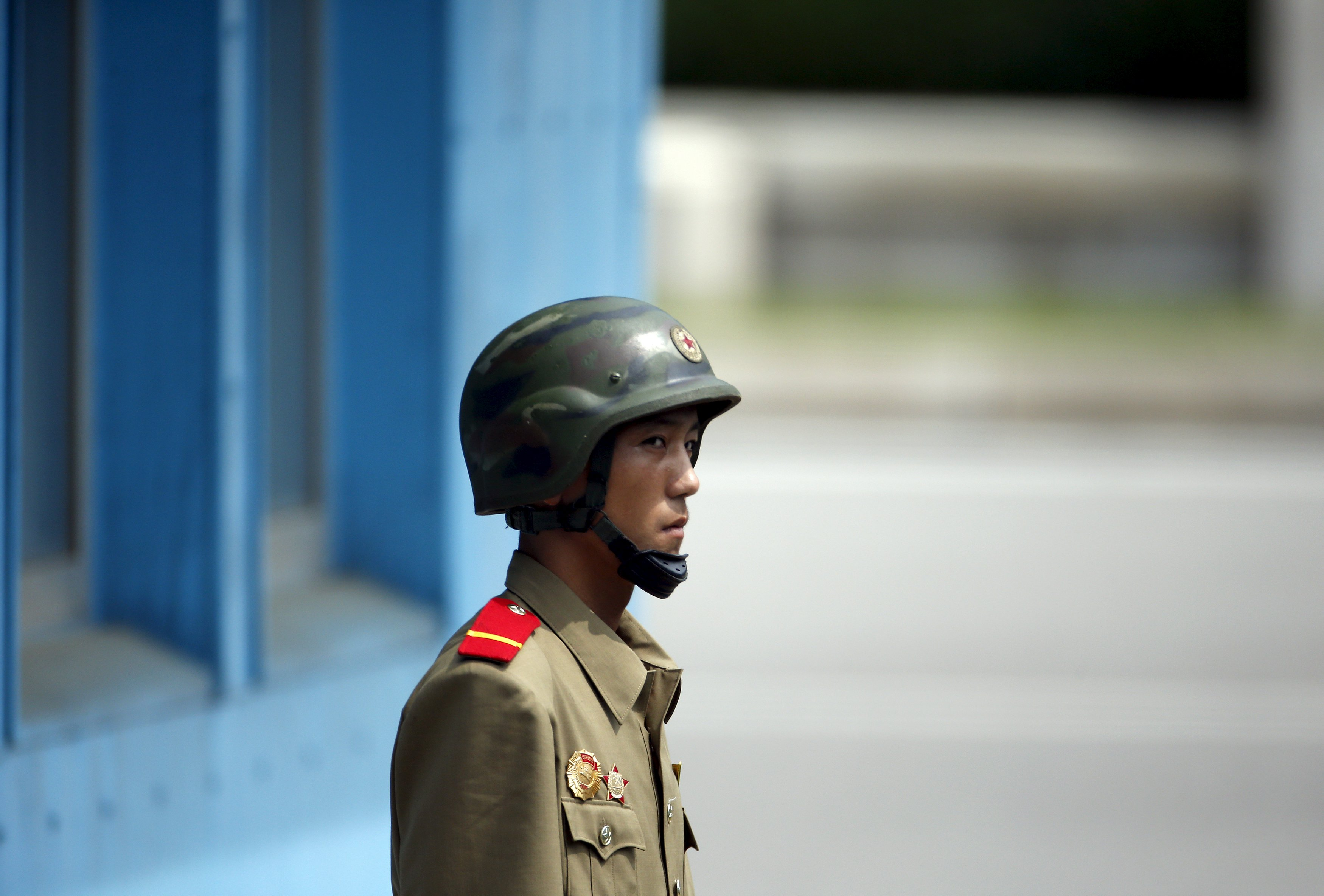 A North Korean soldier keeps watch on the south at the truce village of Panmunjom in the demilitarised zone (DMZ) separating the two Koreas, South Korea, August 11, 2015. South Korea's military on Monday threatened retaliation against North Korea after accusing the North of planting land mines inside the Demilitarised Zone border that wounded two soldiers last week, in what it called a cowardly act of provocation.