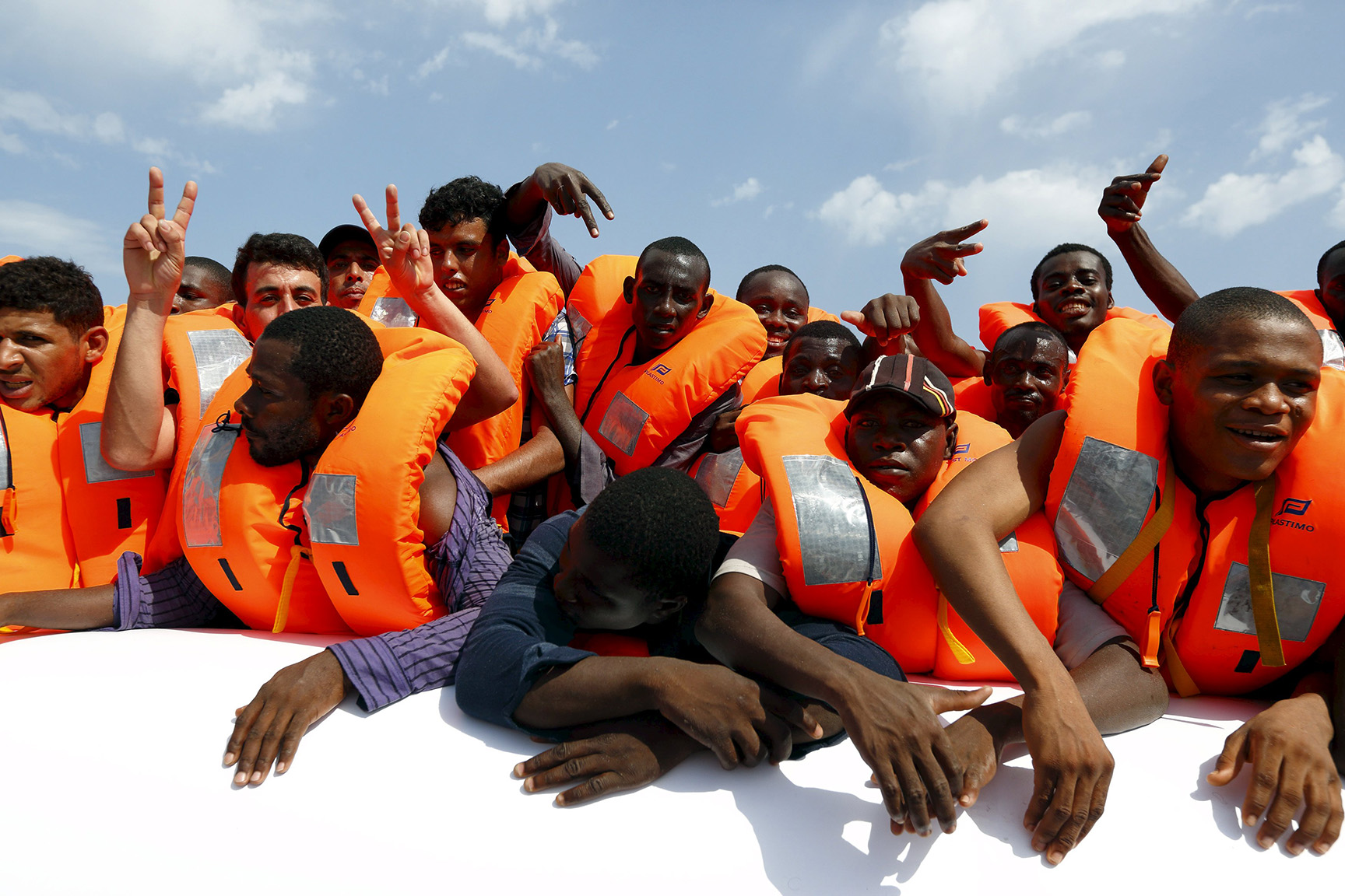 Migrants on a rubber dinghy wait to be rescued by the Migrant Offshore Aid Station ship MV Phoenix off the coast of Libya