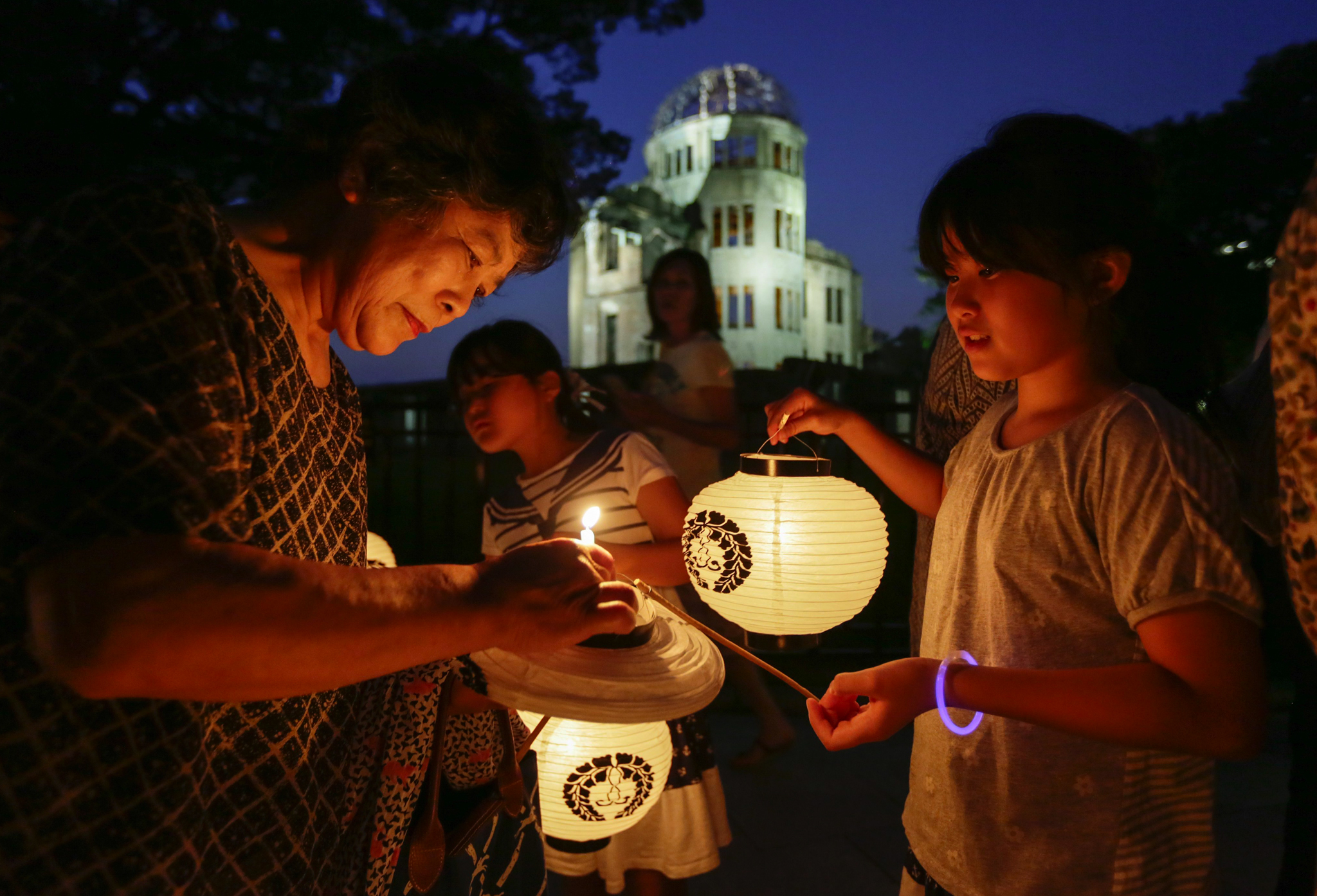 An elderly Hiroshima resident lights the candle of her grand daughter's paper lantern to prepare for a lantern procession to comfort souls of victims killed by the atomic bomb in front of the Atomic Bomb Dome at Hiroshima Peace Memorial Peace Park, in Hiroshima, Japan.