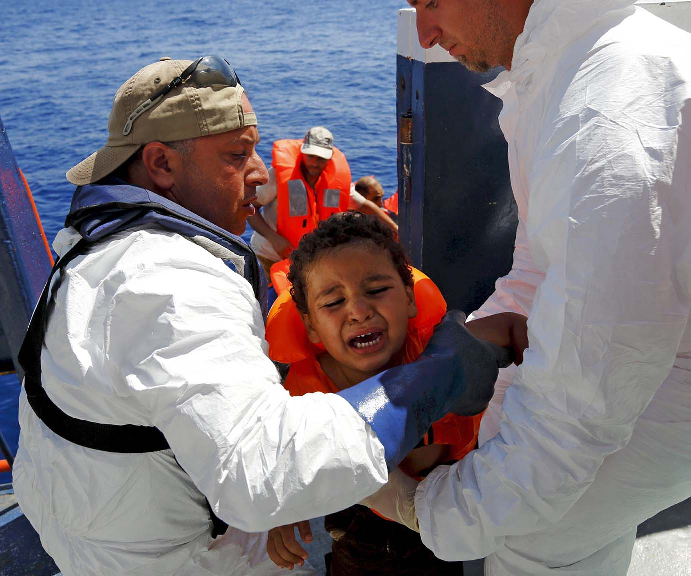 A migrant child is brought onto the Migrant Offshore Aid Station (MOAS) ship