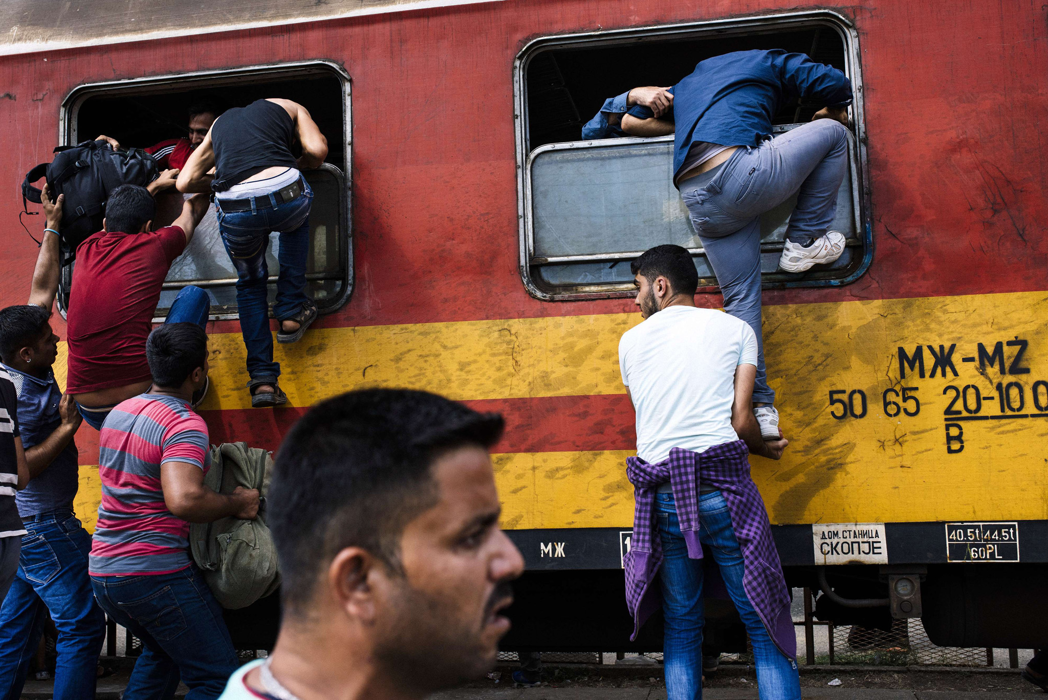 Migrants try to get on a train heading to the border with Serbia at the train station in Gevgelija, on the Macedonian-Greek border. According to the UN, some 224,000 migrants and refugees have crossed the Mediterranean to Europe so far this year.