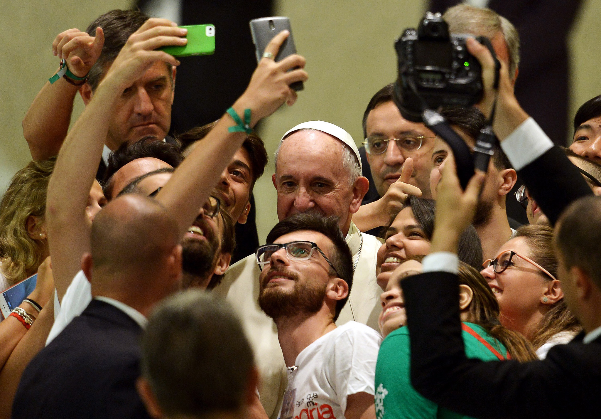 Pope Francis takes a selfie with a group of people during a meeting with the Youth Eucharistic Movement in the Paul VI hall at the Vatican.