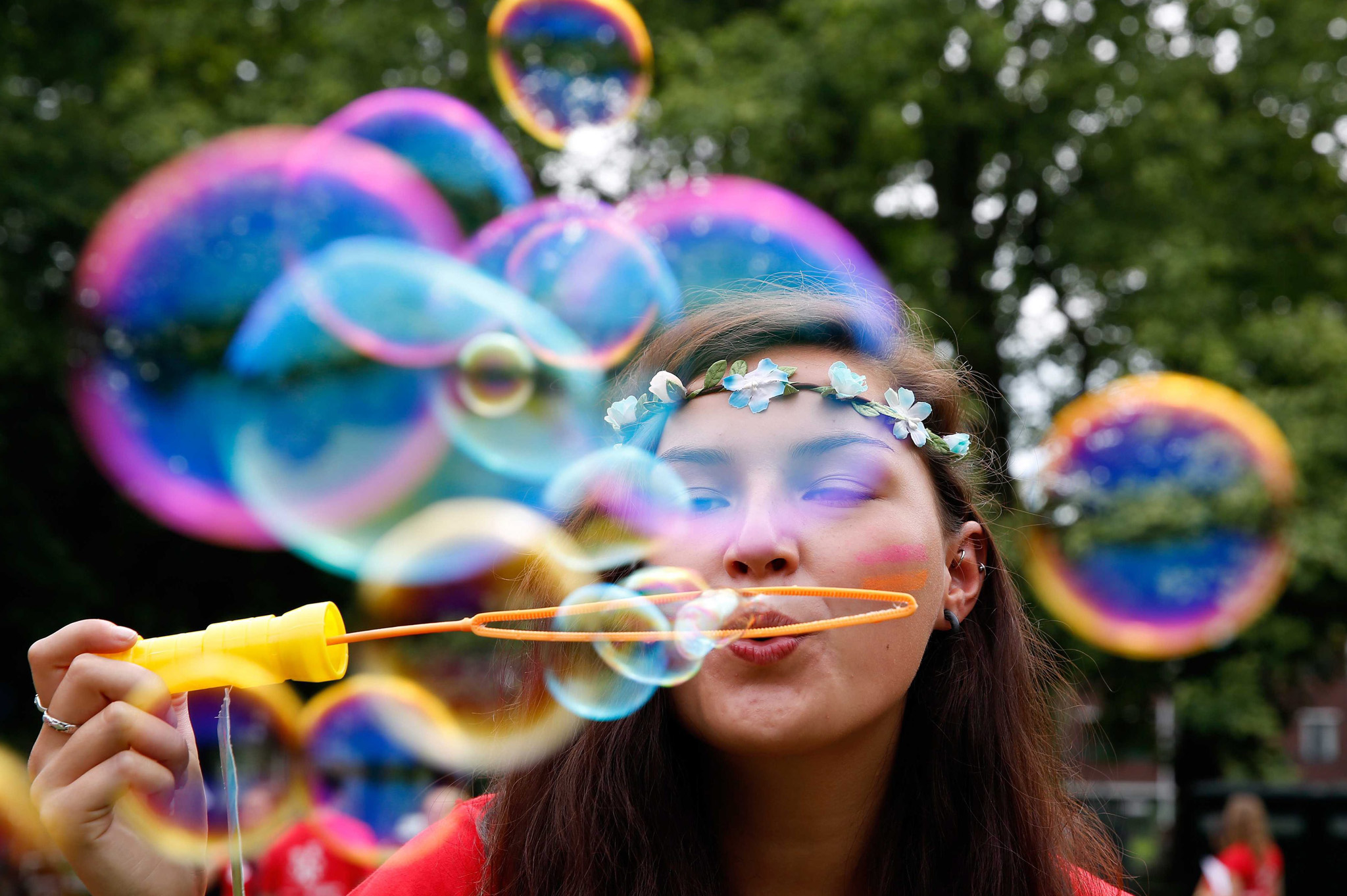 A student blows bubbles on the first day of the university introduction days for students in the Wilhelminapark in Utrecht, the Netherlands.