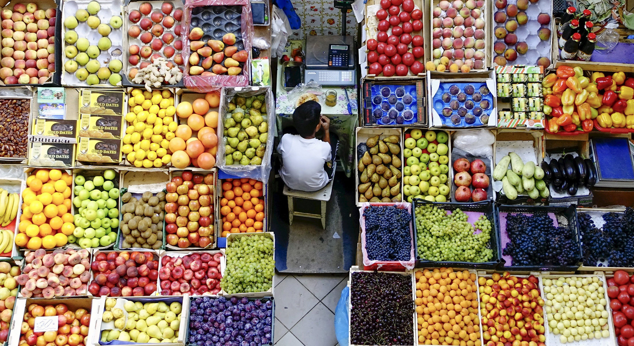 A boy takes a meal break at a fruit stall in the central market in Kazan, Russia.