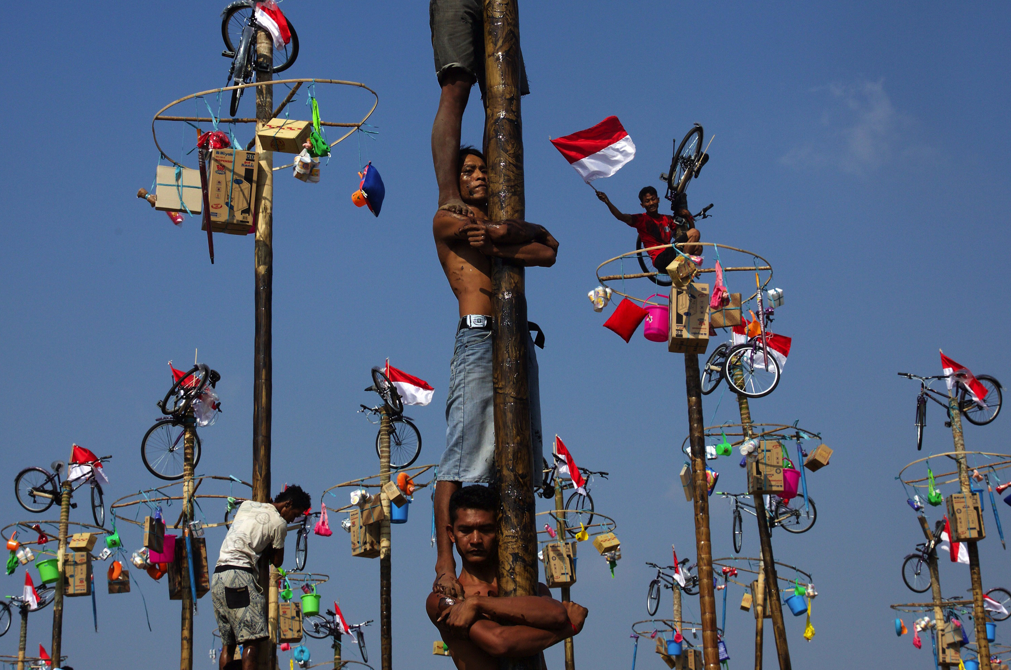 Indonesian men in teams of 4 try to climb to the top of a greased pole called a panjat pinang in order to get to the prizes tied to the top in Jakarta, Indonesia. Cities and villages across Indonesia celebrated the country's 70th anniversary of Independence with traditional games, and music, and flag raising ceremonies