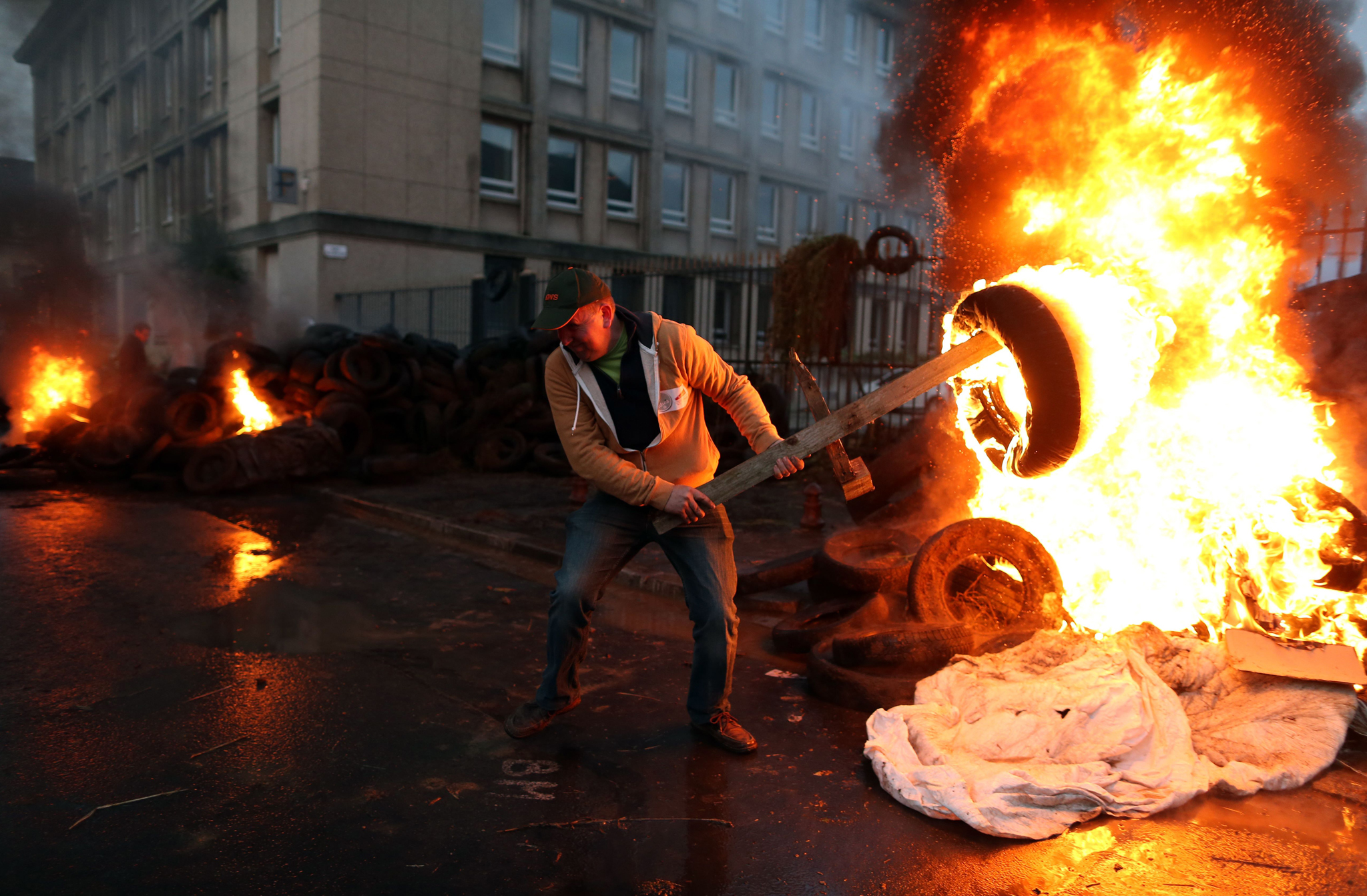 A man prepares to throw a burning tyre as farmers protest in front of the prefecture in Saint-Lo, northwestern France.