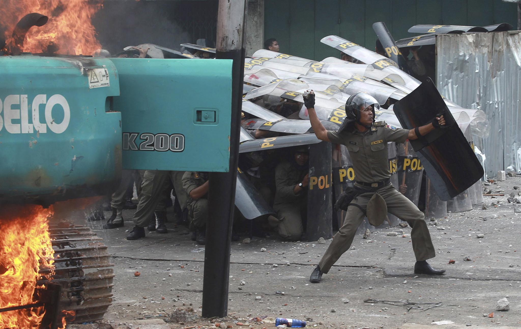 A municipal police officer throws a stone back at protesting residents of Kampung Pulo after clashes erupted during an eviction in Jakarta