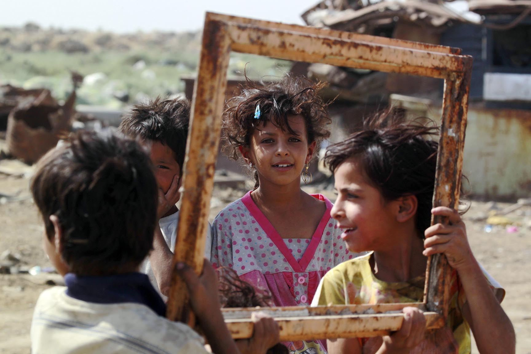 Iraqi children hold an empty frame at a garbage dump
