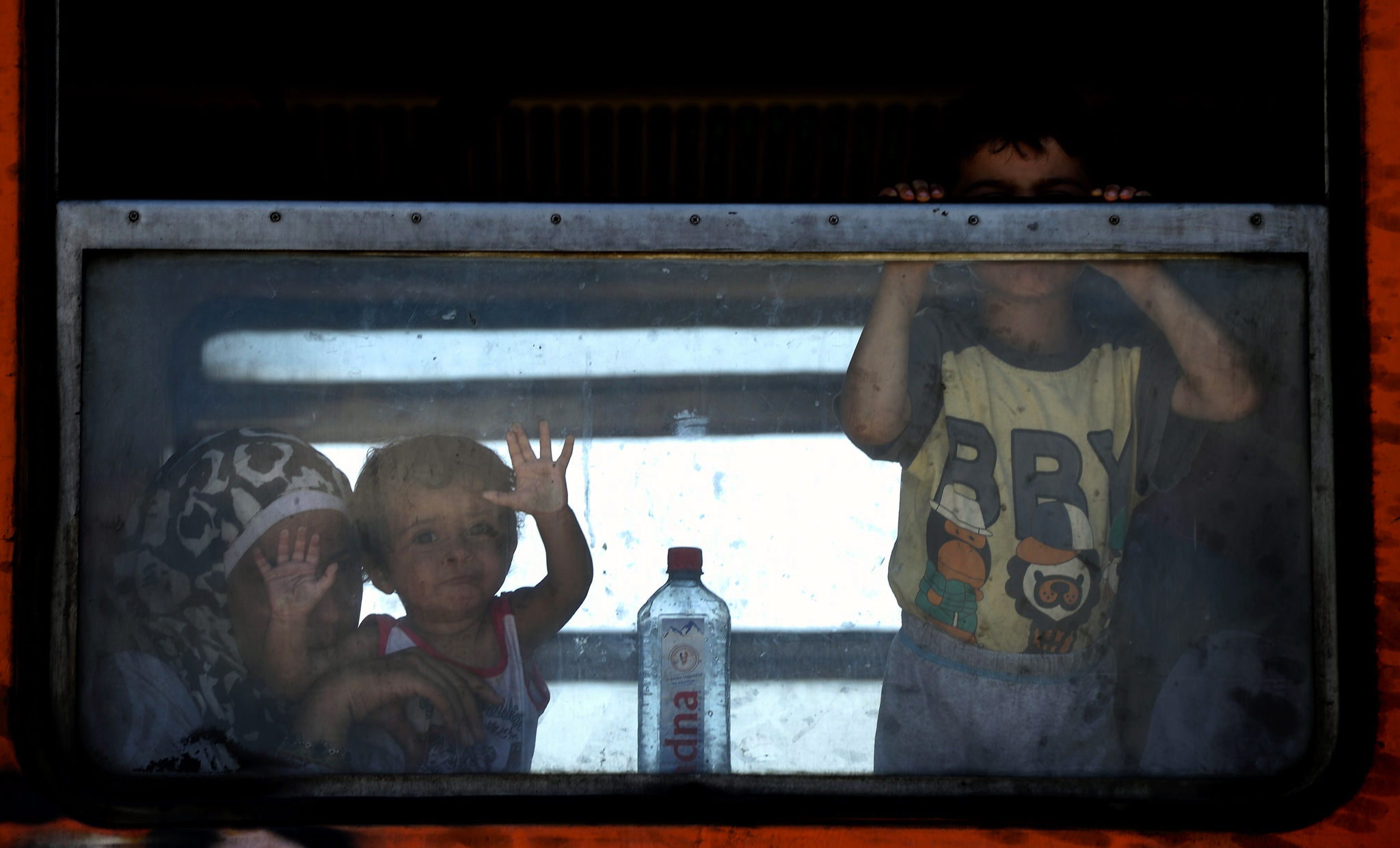 A mother and children look through a train window at Gevgelija, Macedonia, as migrants continue their journey towards other EU countries.