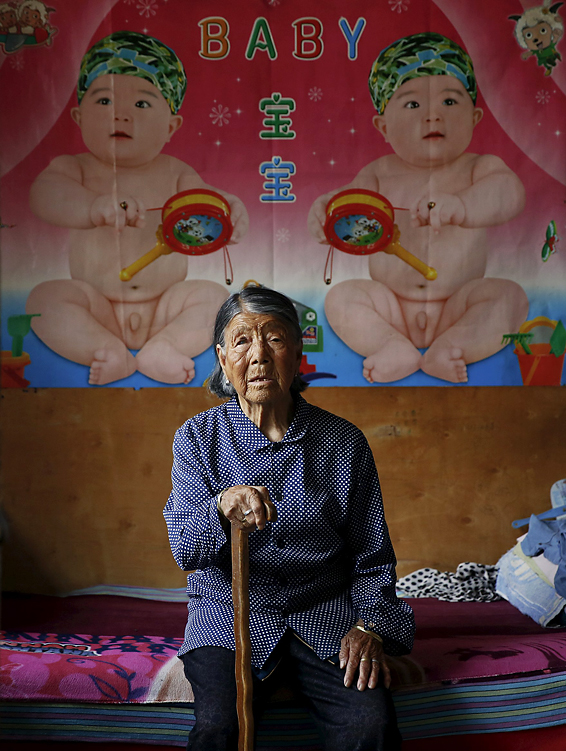 "Wider Image: ""Comfort Woman"" Survivors Tell Their Stories...Former Chinese ""comfort woman"" Hao Yuelian sits on her bed under pictures of babies at her house in Taiyuan, Shanxi Province, China, July 16, 2015. ""Comfort women� is the Japanese euphemism for women who were forced into prostitution and sexually abused at Japanese military brothels before and during World War Two. Her adopted daughter explained that the biggest scar of her life was her lost fertility, something her family considers is related to what happened to Hao during World War Two. Losing her fertility is the biggest regret of her life so she puts up posters of babies in her room to sooth herself. According to the information from China's Commission of Inquiry into the Facts of Comfort Women being Victims, which is based on her own statement during the commission's research, Hao was abducted by Japanese soldiers at 17 and was forced to serve as a ""comfort woman"" for over 20 days during World War Two.  REUTERS/Kim Kyung-Hoon TPX IMAGES OF THE DAYPICTURE 19 OF 33 FOR WIDER IMAGE STORY ""COMFORT WOMAN SURVIVORS TELL THEIR STORIES"" SEARCH ""KIM COMFORT"" FOR ALL PICTURES"