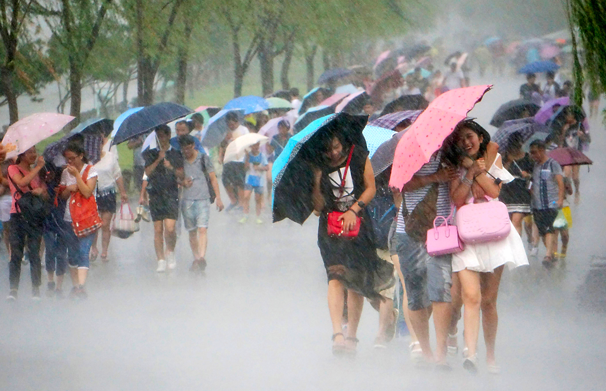 "Typhoon ""Soudelor"" Approaches To Southeast China...HANGZHOU, CHINA - AUGUST 07: (CHINA OUT) Paople use umbrellas as they walk in strong wind and heavy rain near West Lake as Typhoon ""Soudelor"" approaches on August 7, 2015 in Hangzhou, Zhejiang Province of China. Typhoon ""Soudelor"" will land on southeastern China's coastal areas this weekend, according to meteorological departments.  (Photo by ChinaFotoPress/Getty Images)"