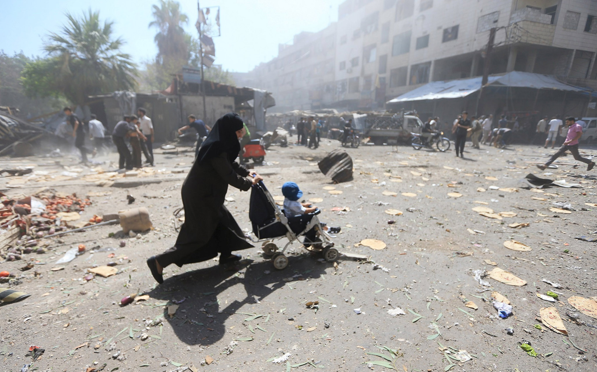 A woman pushes a baby stroller as she rushes away after what activists said were airstrikes by forces loyal to Syria's President Bashar al-Assad on a busy marketplace in the Douma neighborhood of Damascus, Syria...A woman pushes a baby stroller as she rushes away after what activists said were airstrikes by forces loyal to Syria's President Bashar al-Assad on a busy marketplace in the Douma neighborhood of Damascus, Syria August 12, 2015. Syrian government air strikes on rebel-held areas near Damascus killed at least 31 people on Wednesday, and insurgents bombarded the capital with rockets that killed at least 13 people, the Syrian Observatory for Human Rights reported. REUTERS/Bassam Khabieh   NO ARCHIVES