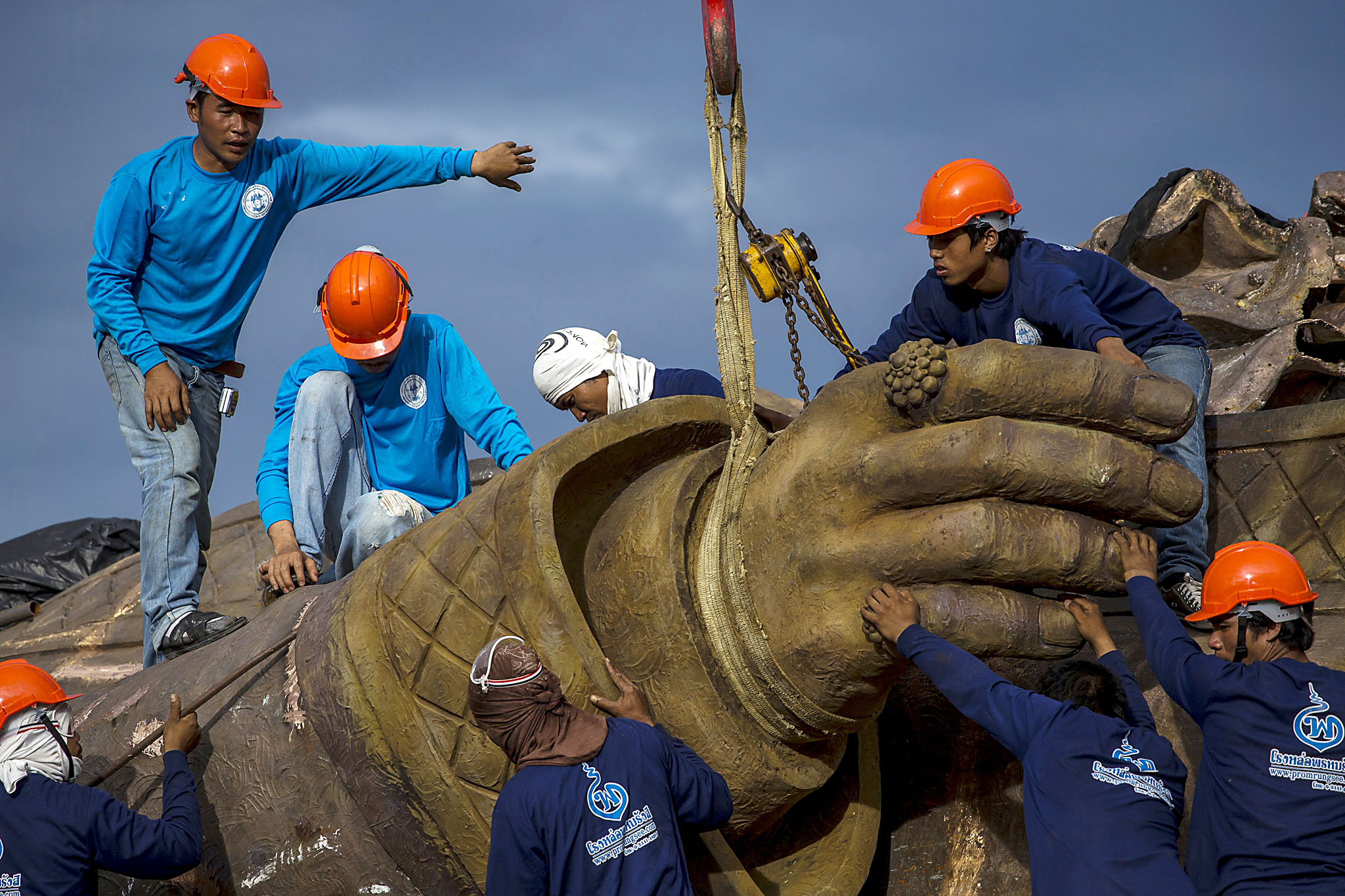 Labourers use a crane to lift the hand of a giant bronze statue of former King Rama I at Ratchapakdi Park in Hua Hin...Labourers use a crane to lift the hand of a giant bronze statue of former King Rama I at Ratchapakdi Park in Hua Hin, Prachuap Khiri Khan province, Thailand, August 4, 2015. The park is being constructed by the Thai army to honor past Thai monarchs and is situated on an army compound near the Klai Kangwon Palace. The project is estimated to cost about 700 million baht ($20,073,991), according to local media. REUTERS/Athit Perawongmetha TPX IMAGES OF THE DAY