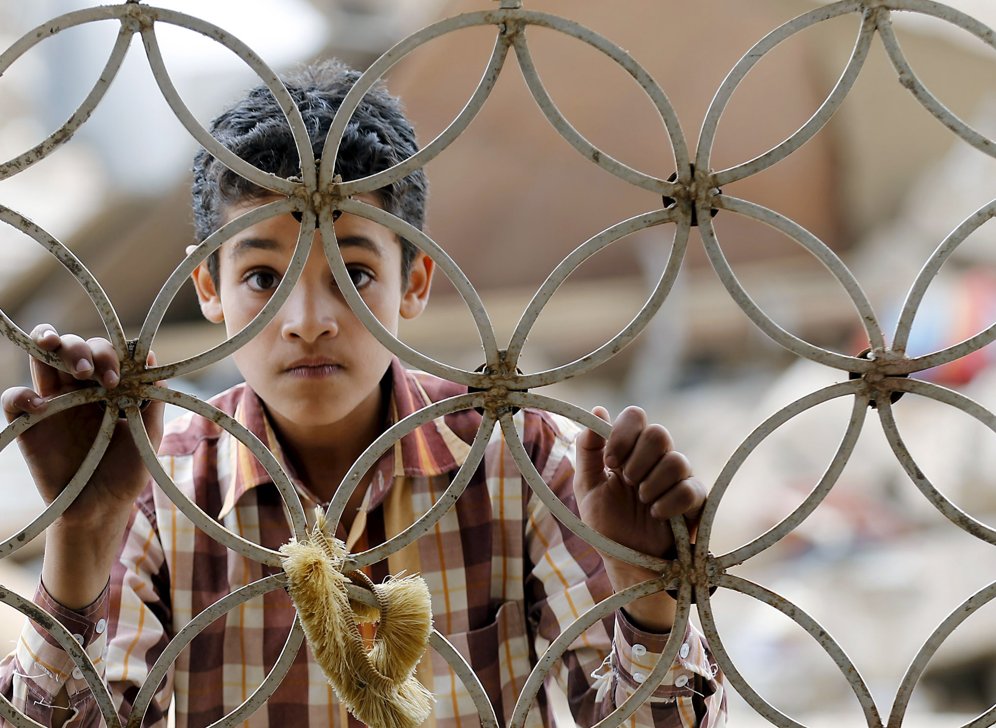 A boy looks through the window grills of a house that was damaged by a Saudi-led air strike in Yemen's capital Sanaa...A boy looks through the window grills of a house that was damaged by a Saudi-led air strike in Yemen's capital Sanaa August 26, 2015. Yemeni army units allied to the Houthi militia fired a ballistic missile toward southern Saudi Arabia on Wednesday, the group's TV channel said, as combat between the kingdom and the Iran-allied group has intensified. REUTERS/Khaled Abdullah