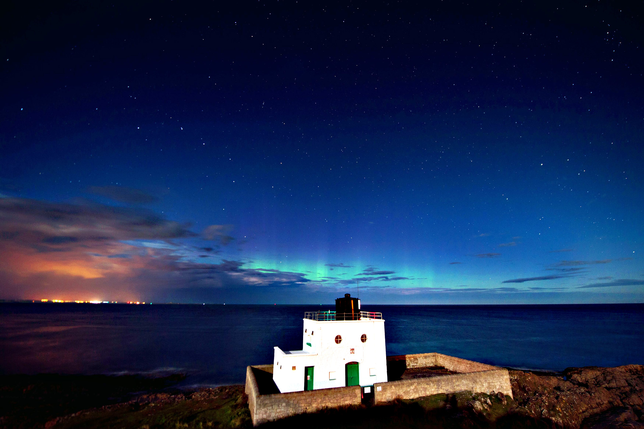 Summer weather Aug 27th 2015...A faint Aurora can be seen over Bamburgh lighthouse in Northumberland the early hours of this morning. PRESS ASSOCIATION Photo. Picture date: Thursday August 27, 2015