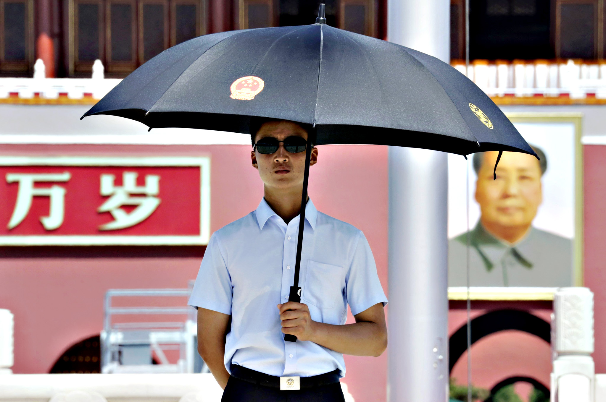 A paramilitary police officer in plain-clothes holding an umbrella keeps watch on Beijing's Tiananmen Square, on Thursday. Major Western leaders will not attend a military parade in China next week to mark the end of World War Two, leaving President Xi Jinping to stand with leaders and officials from Russia, Sudan, Venezuela and North Korea at his highest-profile event of 2015